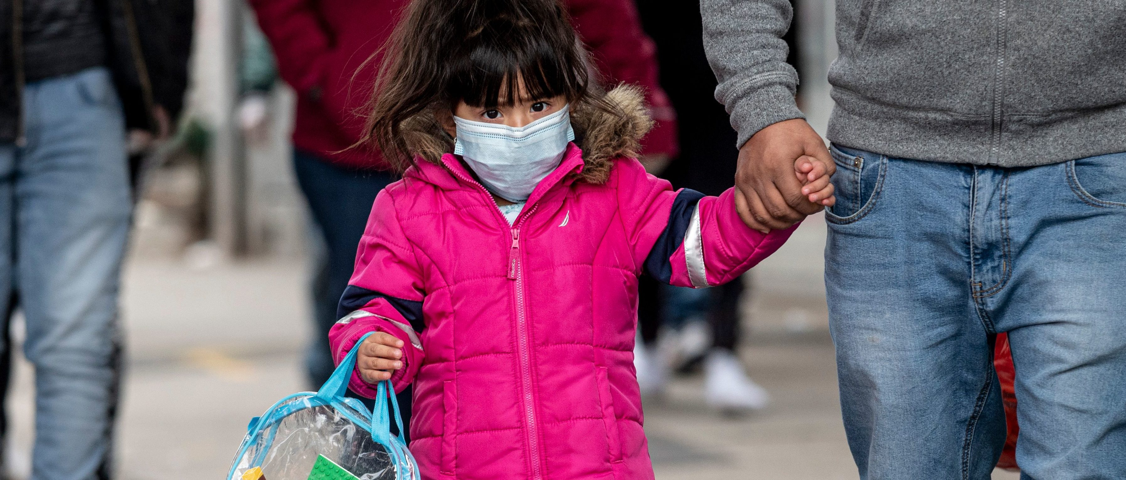 A girl, wearing a mask, walks down a street in the Corona neighborhood of Queens on April 14, 2020 in New York City. - New York will start making tens of thousands of coronavirus test kits a week, its mayor announced Tuesday, as the city looks to boost testing capacity with a view to ending its shutdown. (Photo by Johannes EISELE / AFP) (Photo by JOHANNES EISELE/AFP via Getty Images)