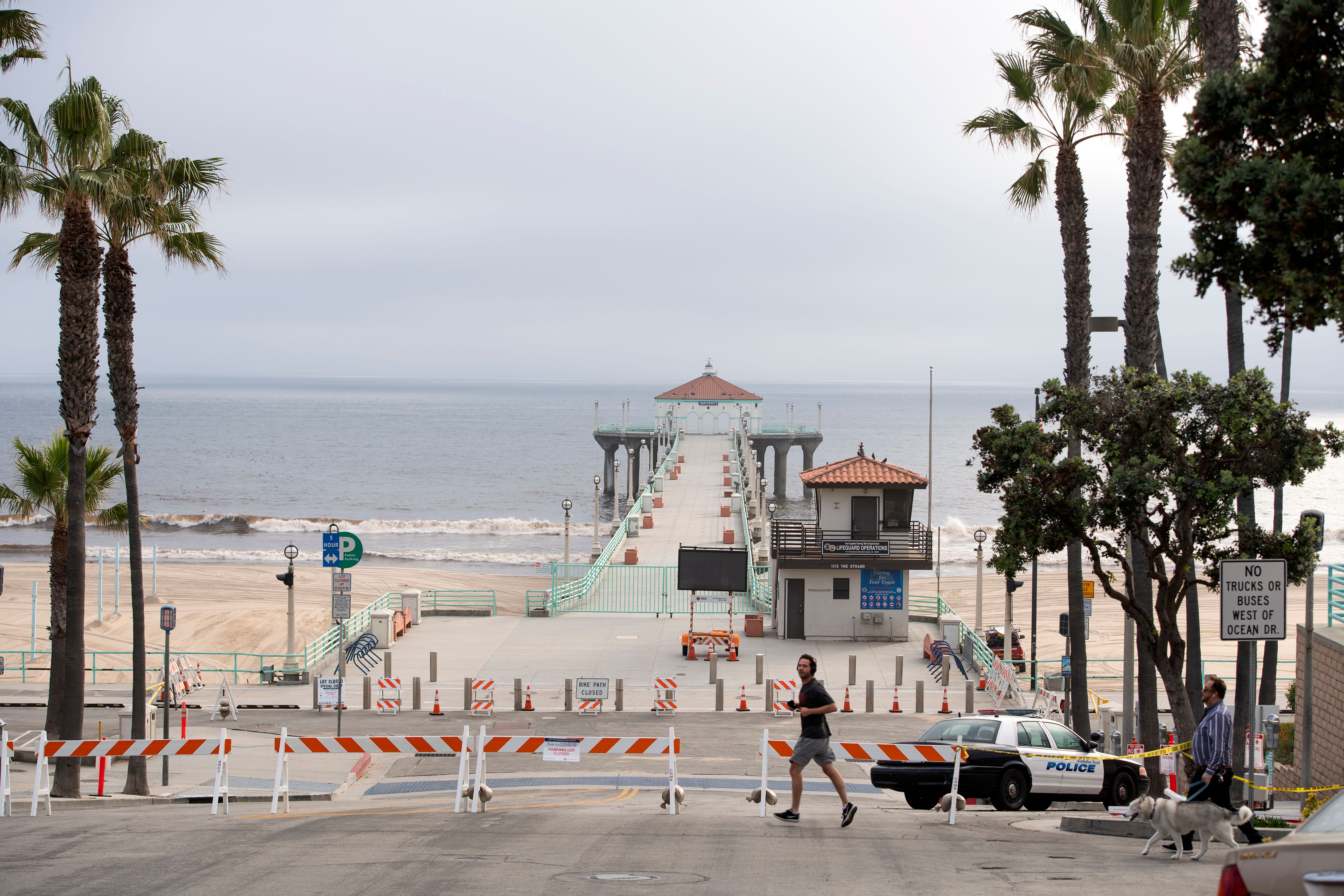 People walk by the closed pier, beach and strand amid the novel coronavirus pandemic on April 28, 2020, in Manhattan Beach, California. (Photo by VALERIE MACON/AFP via Getty Images)