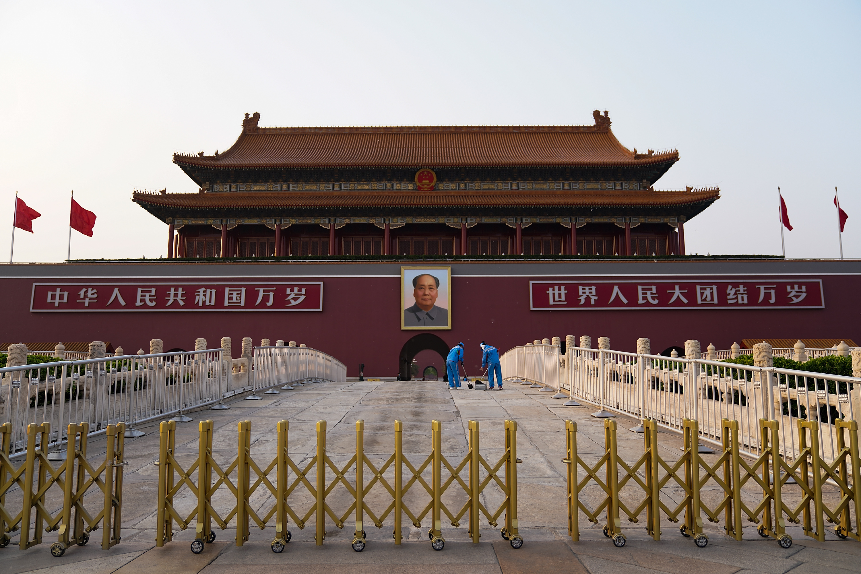 Two cleaners clean the ground in front of the portrait of the late Communist Party leader Mao Zedong on April 29, 2020 in Beijing, China. (Photo by Lintao Zhang/Getty Images)
