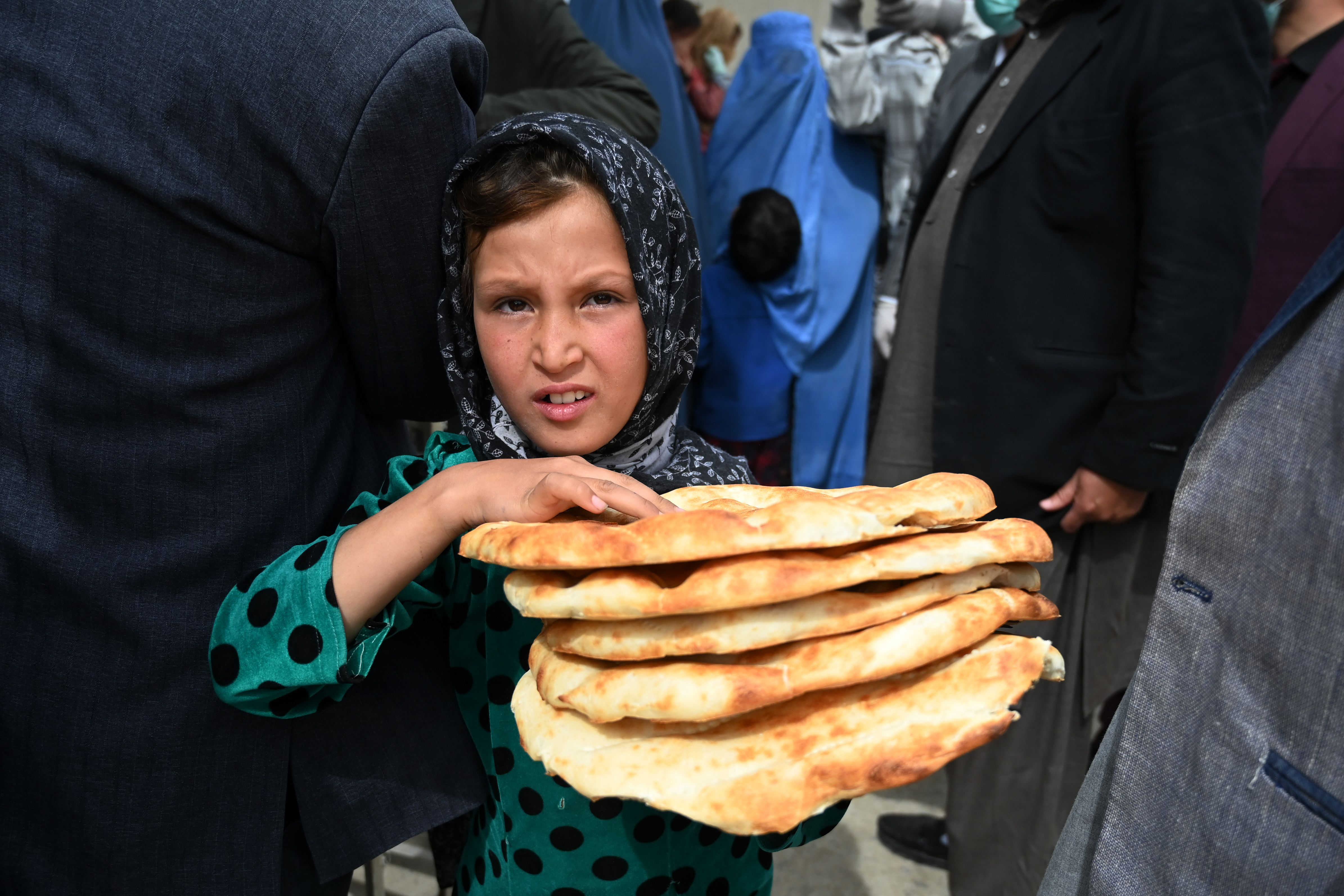 A young girl leaves after receiving free bread from the municipality outside a bakery during the Islamic holy month of Ramadan.(Photo by WAKIL KOHSAR/AFP via Getty Images)