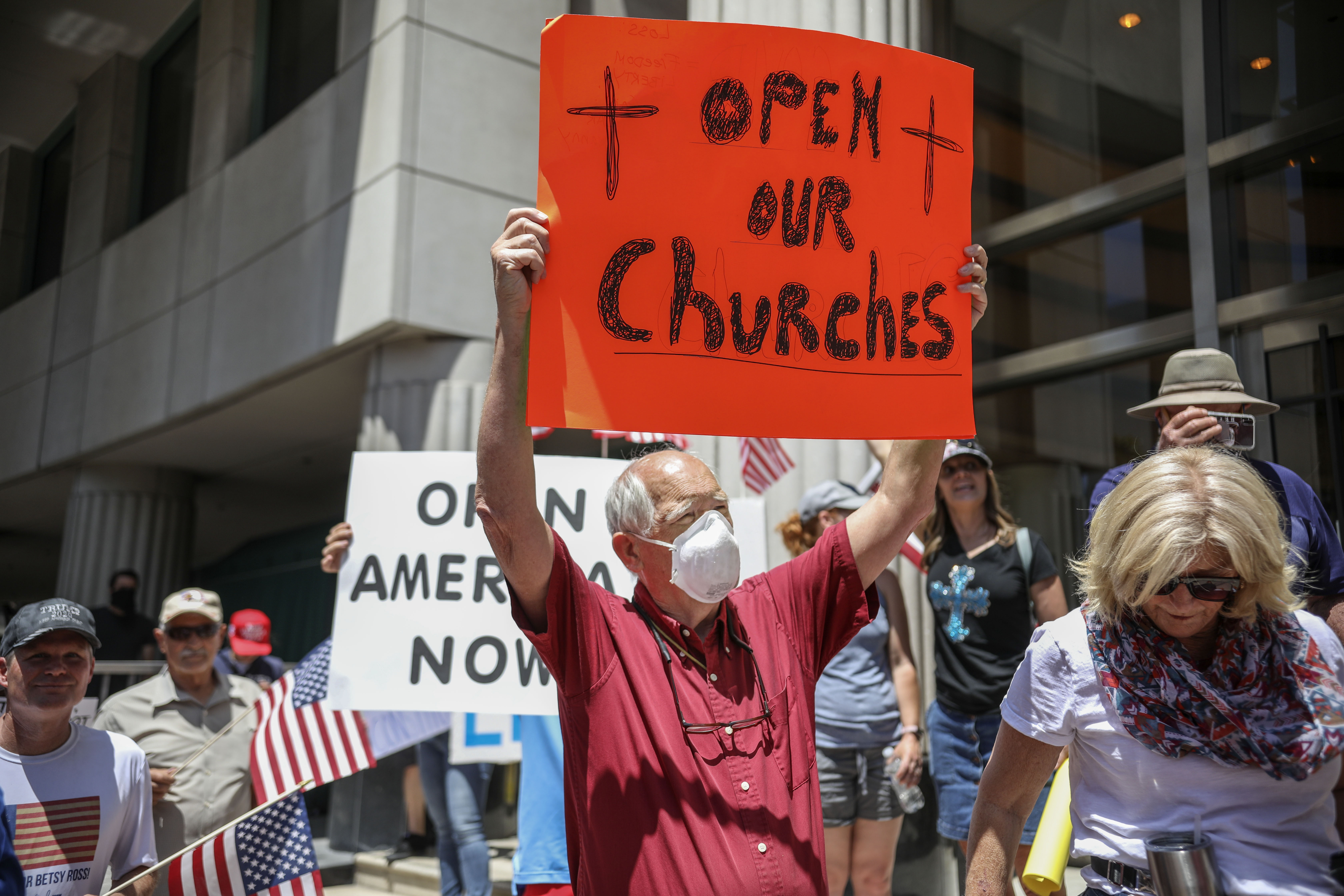 Demonstrators holding signs demanding their church to reopen, protest during a rally to re-open California and against Stay-At-Home directives on May 1, 2020 in San Diego, California. (Photo by SANDY HUFFAKER/AFP via Getty Images)