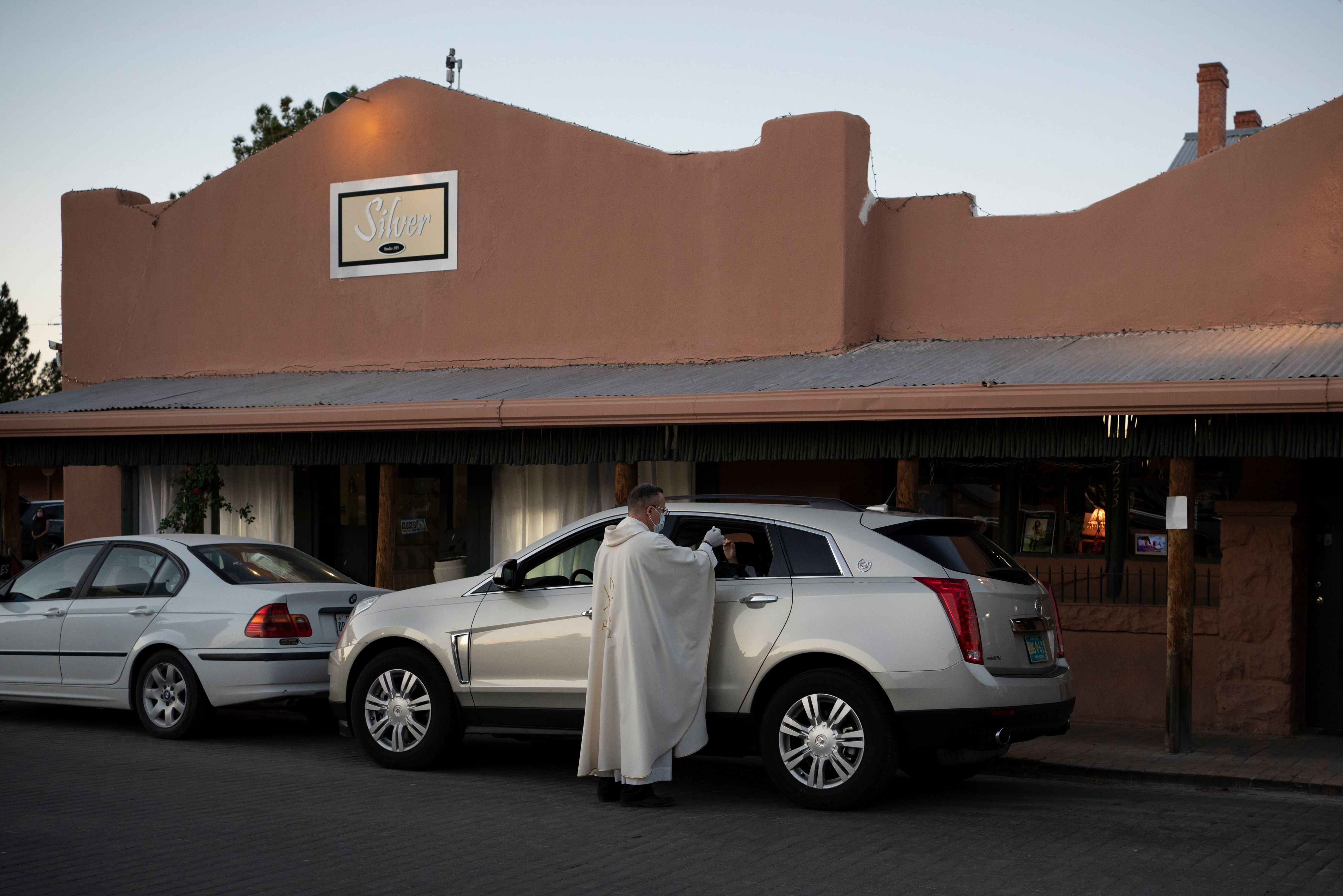 Father Christoper Williams gives communion to parishioners in their cars outside of the Basilica of San Albino on May 2, 2020 in Mesilla, New Mexico, amid the coronavirus pandemic. (Photo by PAUL RATJE/AFP via Getty Images)