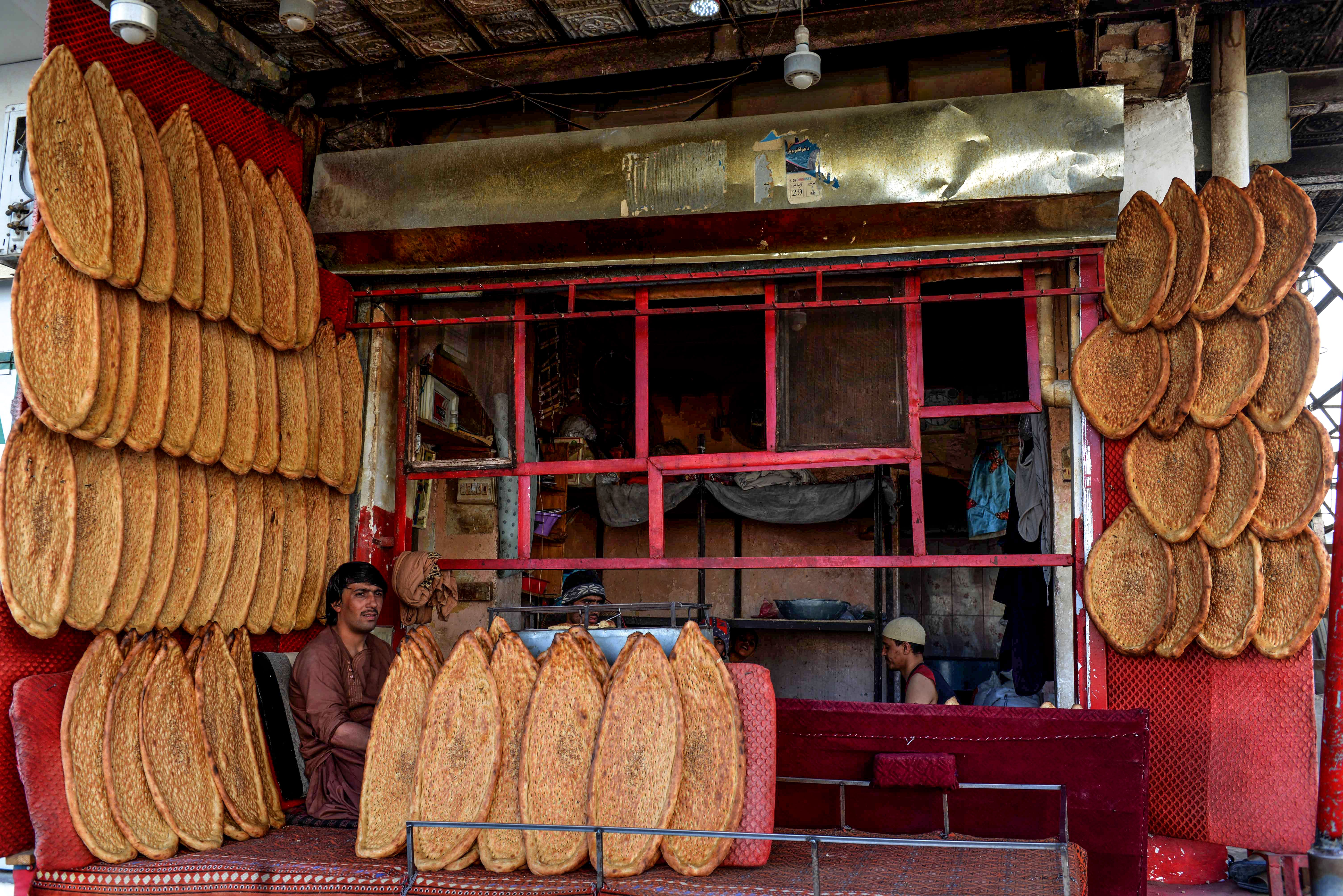 In this photo taken on May 2, 2020, a baker sits inside his bakery among breads as he waits for customers during the Muslim holy month of Ramadan in Kandahar city. (Photo by JAVED TANVEER/AFP via Getty Images)
