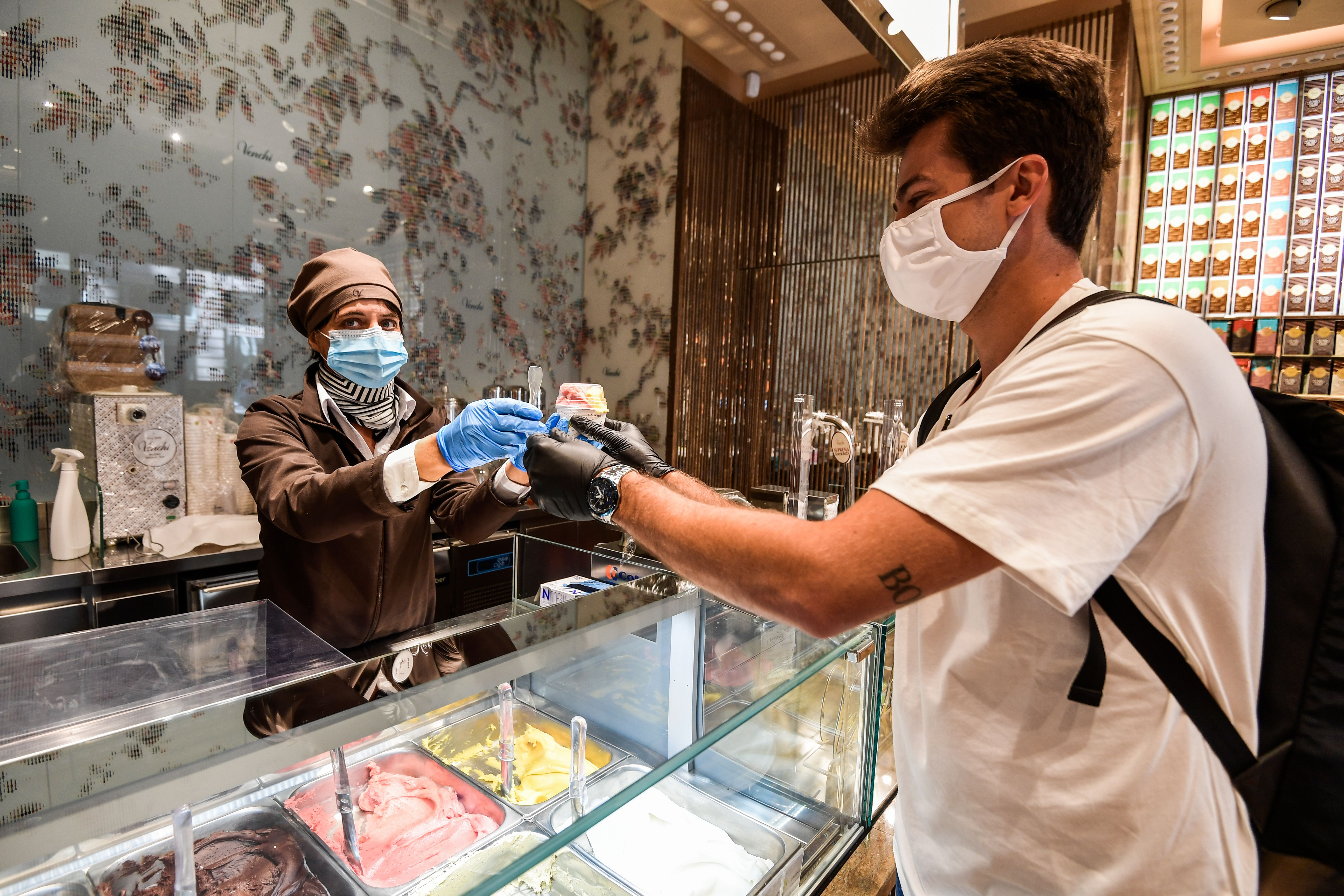 A customer buys takeaway ice cream at the Venchi ice cream parlour on May 4, 2020 in Milan as Italy starts to ease its lockdown. (Photo by MIGUEL MEDINA/AFP via Getty Images)