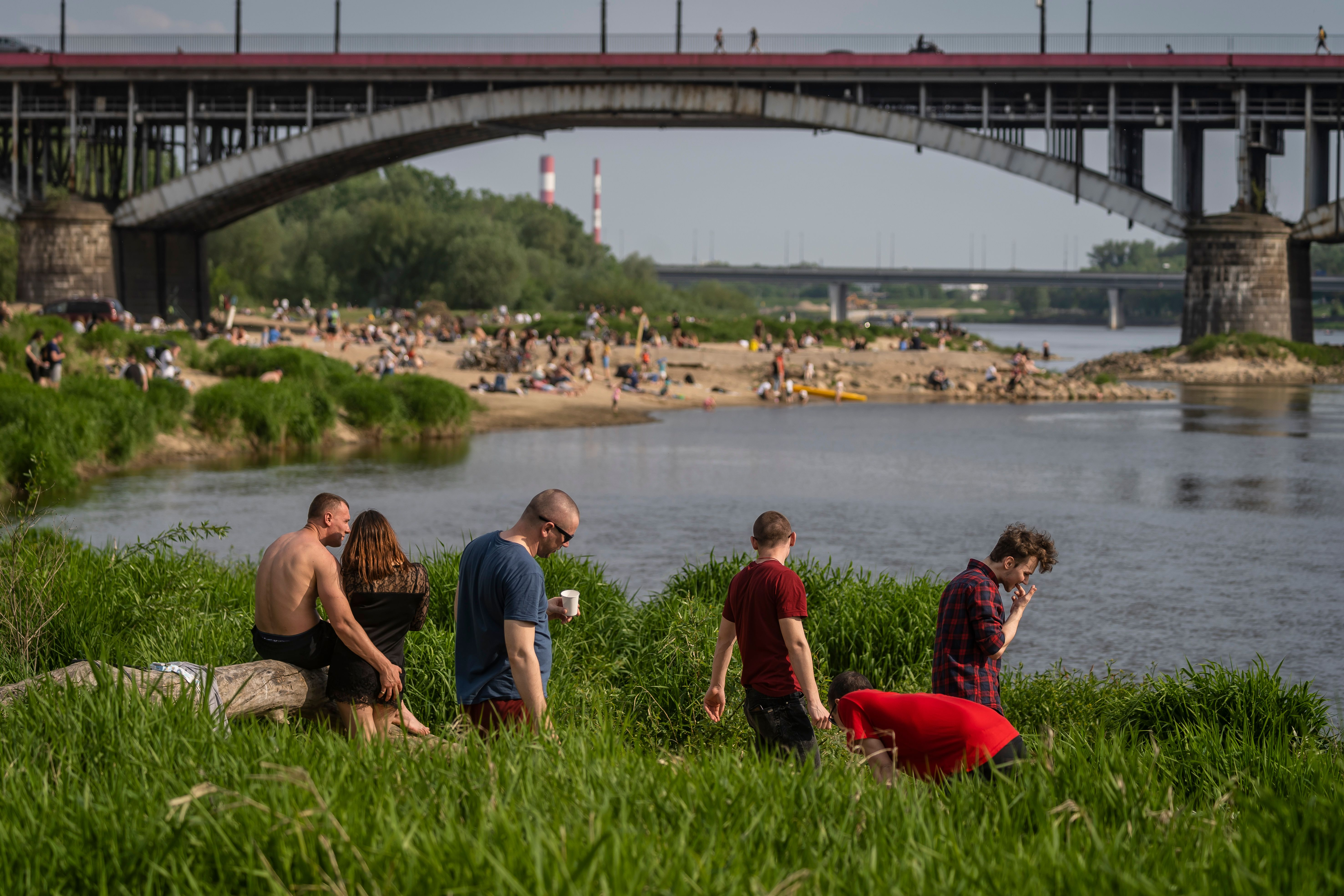 Warsaw residents gather on the bank of the Vistula River to enjoy the warm weather. (Photo by WOJTEK RADWANSKI/AFP via Getty Images)