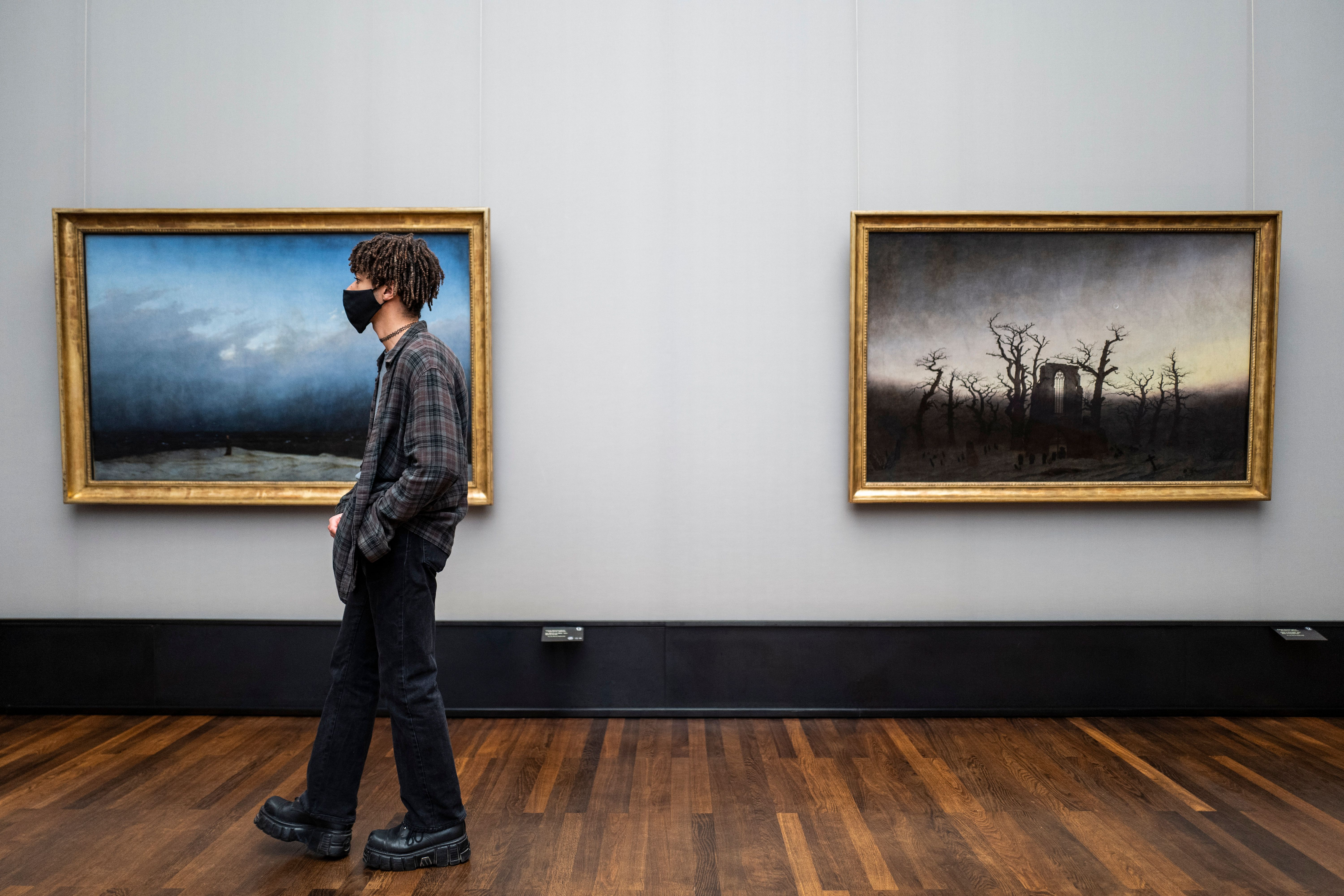 A visitor wearing a face mask walks past two paintings by Caspar David Friedrich at the Alte Nationalgalerie (Old National Gallery) museum in Berlin on May 12, 2020. (Photo by JOHN MACDOUGALL/AFP via Getty Images)