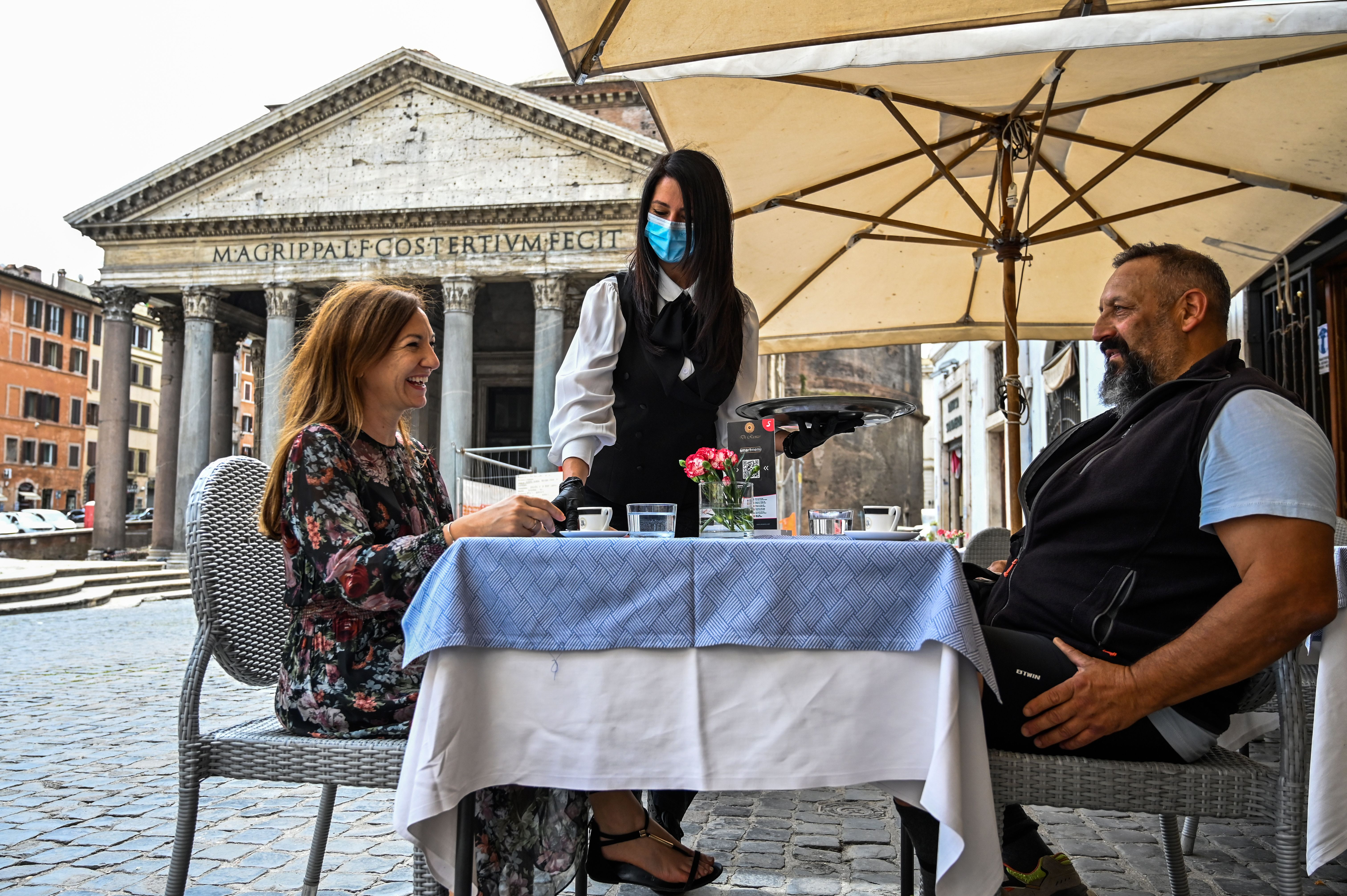 A waiter serves coffee to customers at a cafe terrace by the Pantheon monument in central Rome on May 18, 2020. (Photo by ANDREAS SOLARO/AFP via Getty Images)