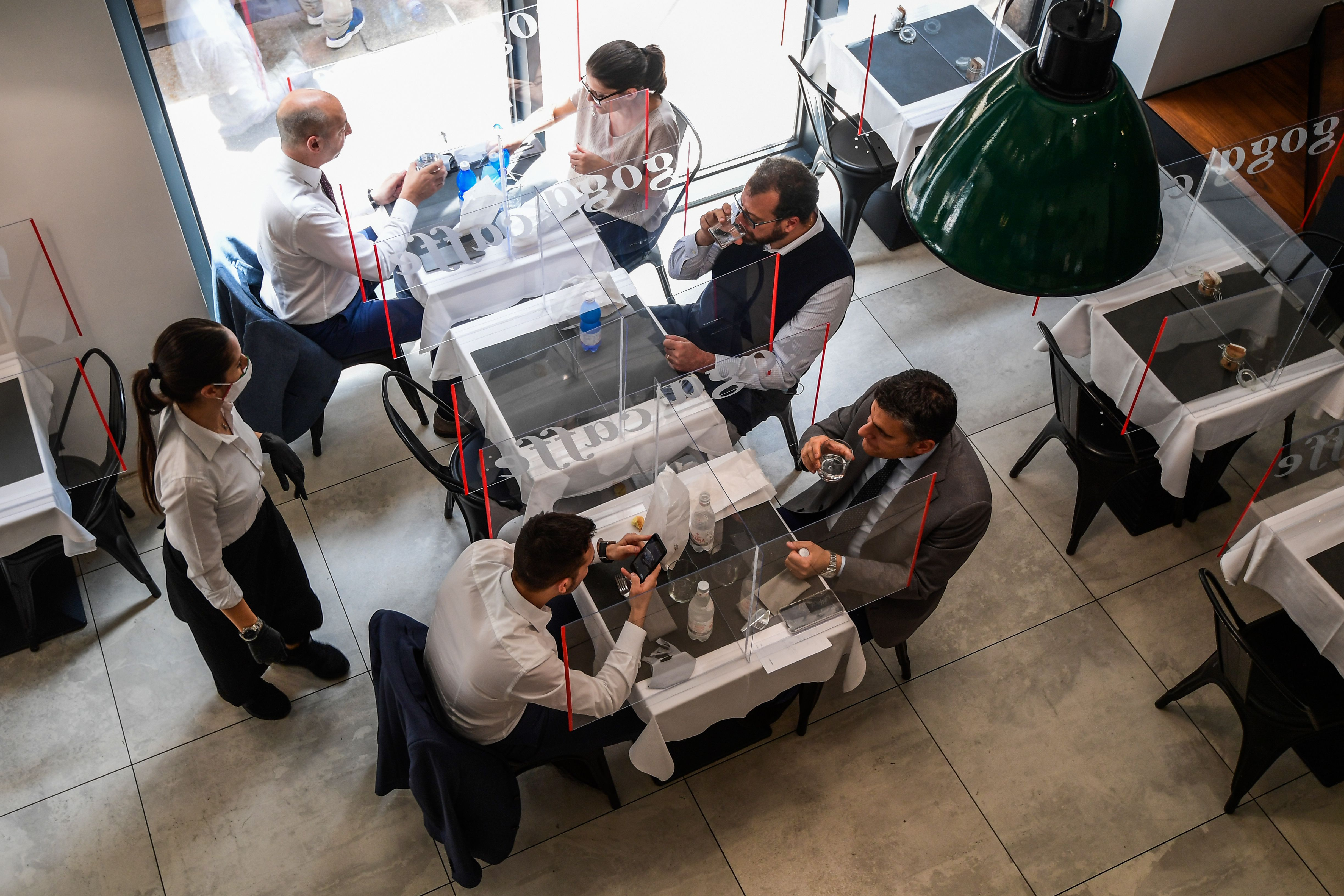 A general view shows people having lunch at tables partitioned with plexiglas at the Goga Cafe on May 18, 2020 in central Milan. (Photo by MIGUEL MEDINA/AFP via Getty Images)