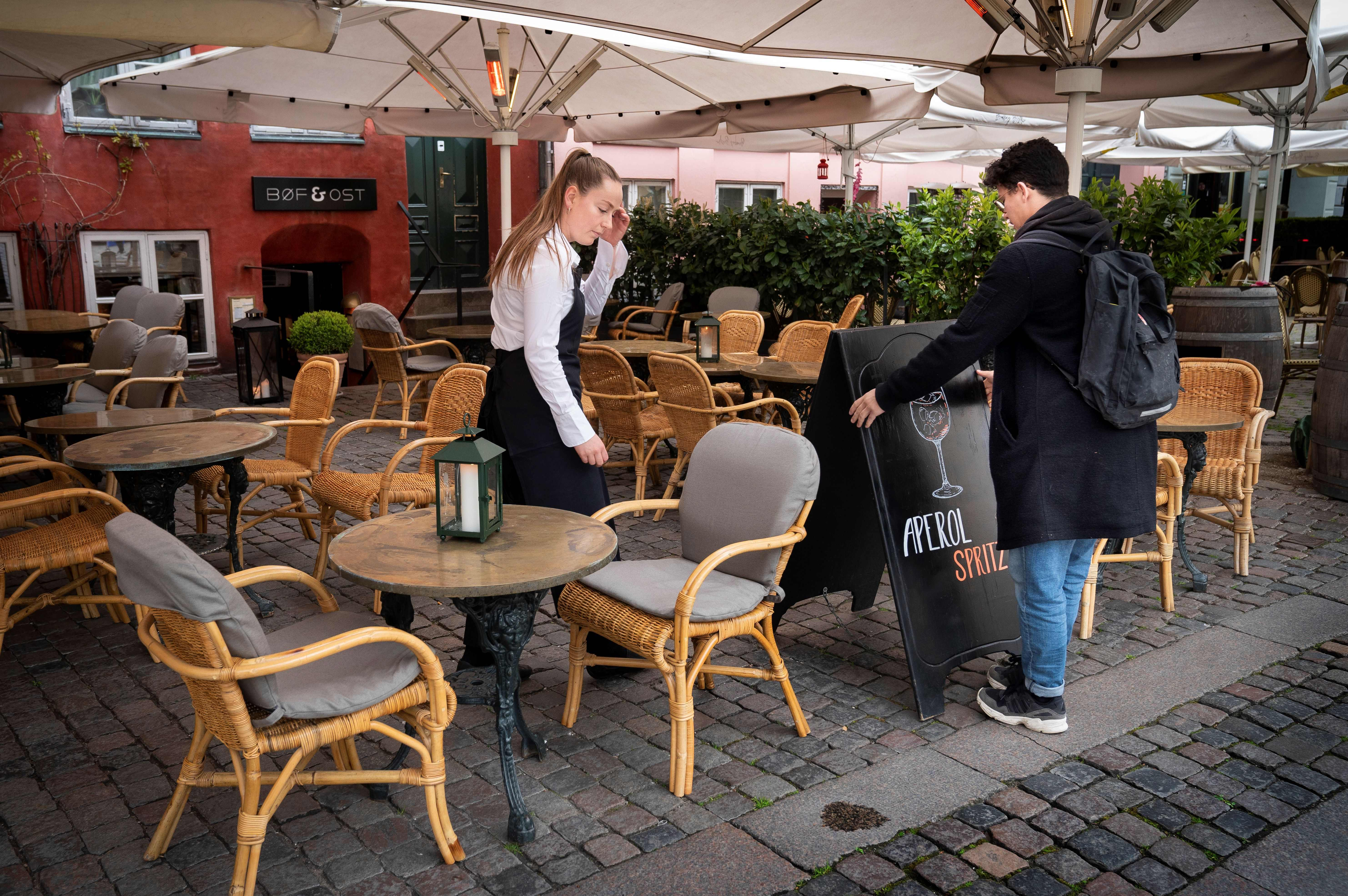 Employees prepare the terrasse of Boef & Ost restaurant at Graabroedre square in Copenhagen before its reopening on May 18, 2020. (Photo by LISELOTTE SABROE/Ritzau Scanpix/AFP via Getty Images)