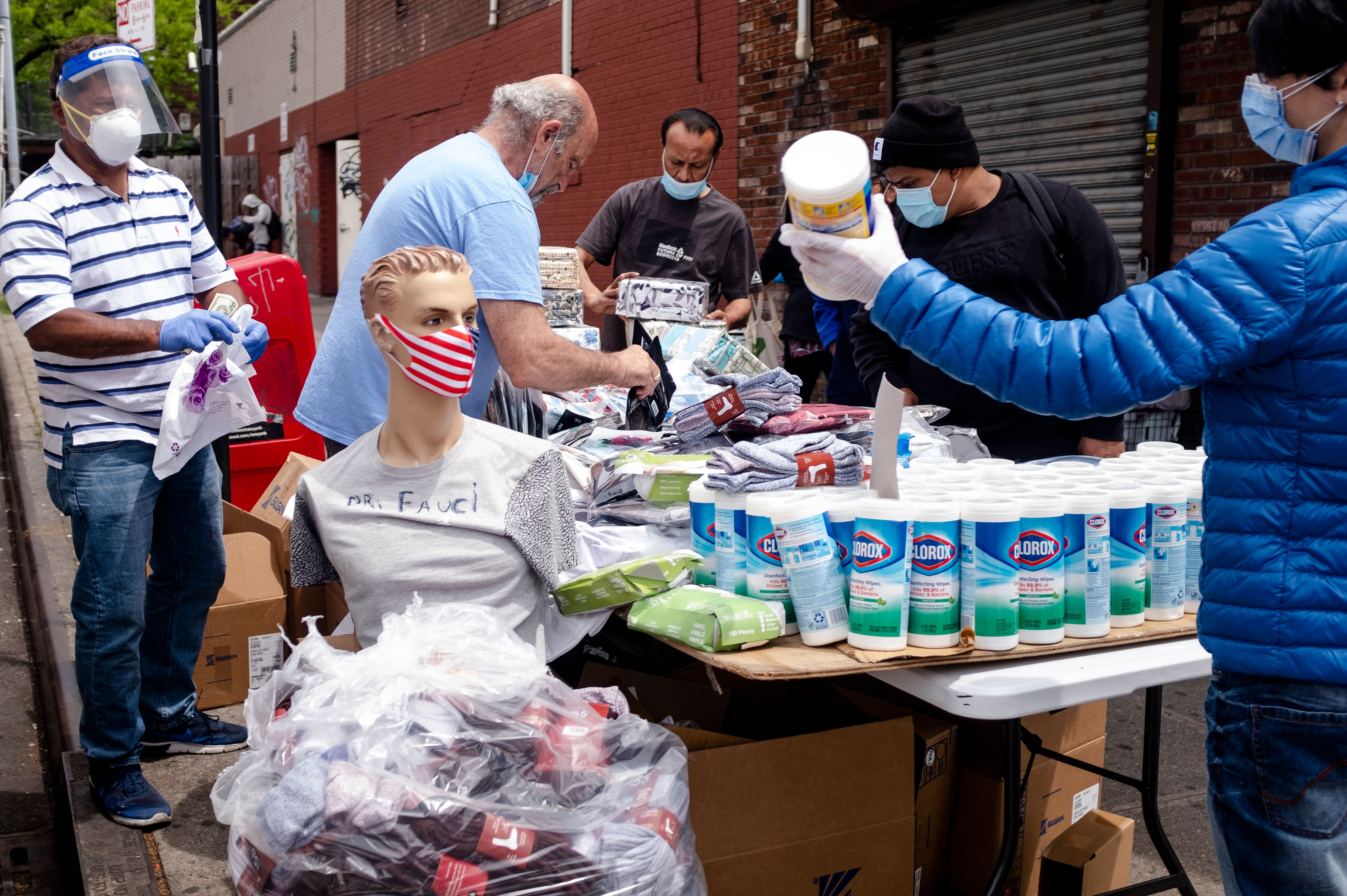 A man sells face masks and disinfection wipes on a street side table on May 18, 2020 in the Elmhurst neighbourhood of Queens in New York City. (Photo by JOHANNES EISELE/AFP via Getty Images)