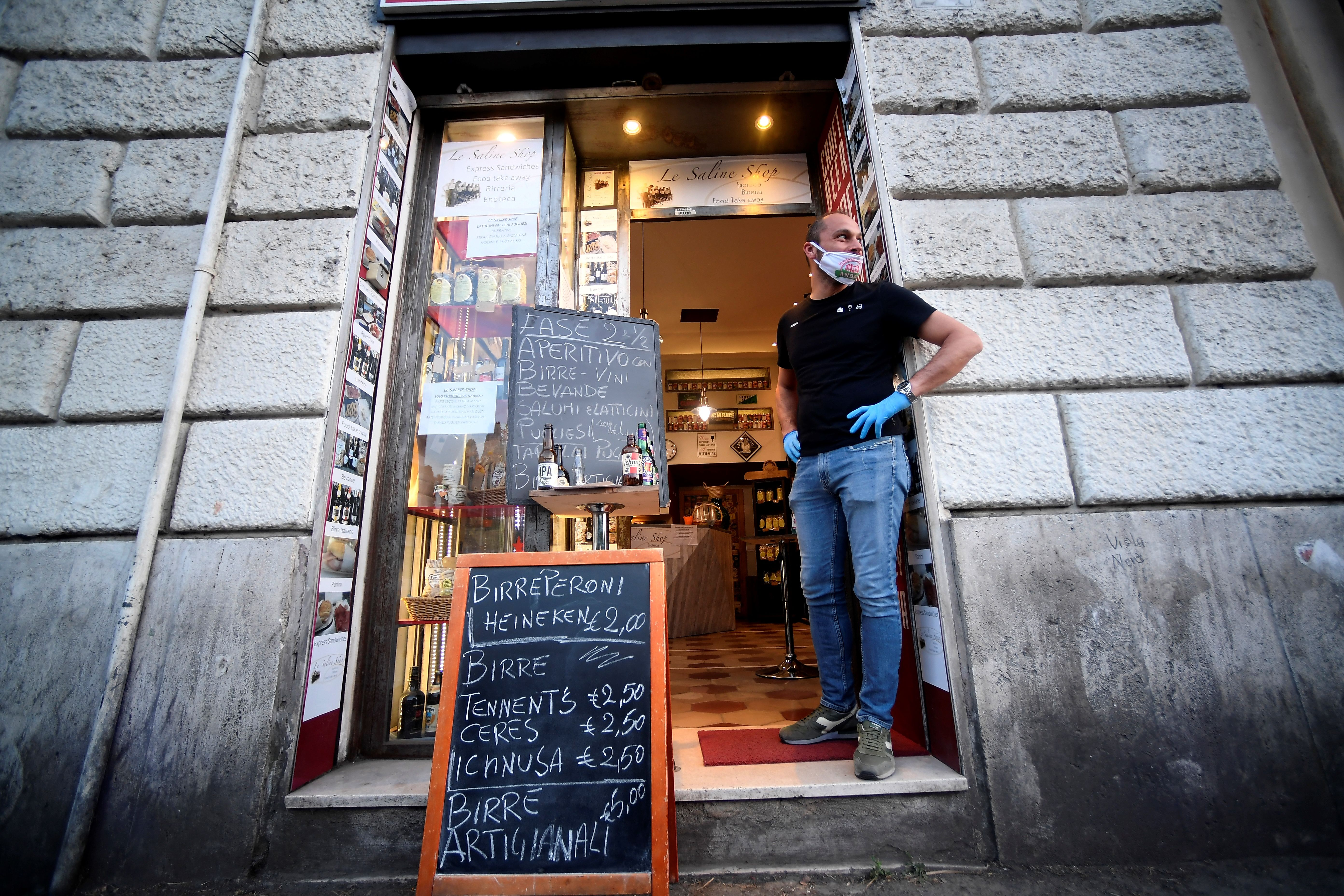 A bar owner waits for aperitif customers outside a bar by the colosseum in Rome, on May 18, 2020. (Photo by FILIPPO MONTEFORTE/AFP via Getty Images)