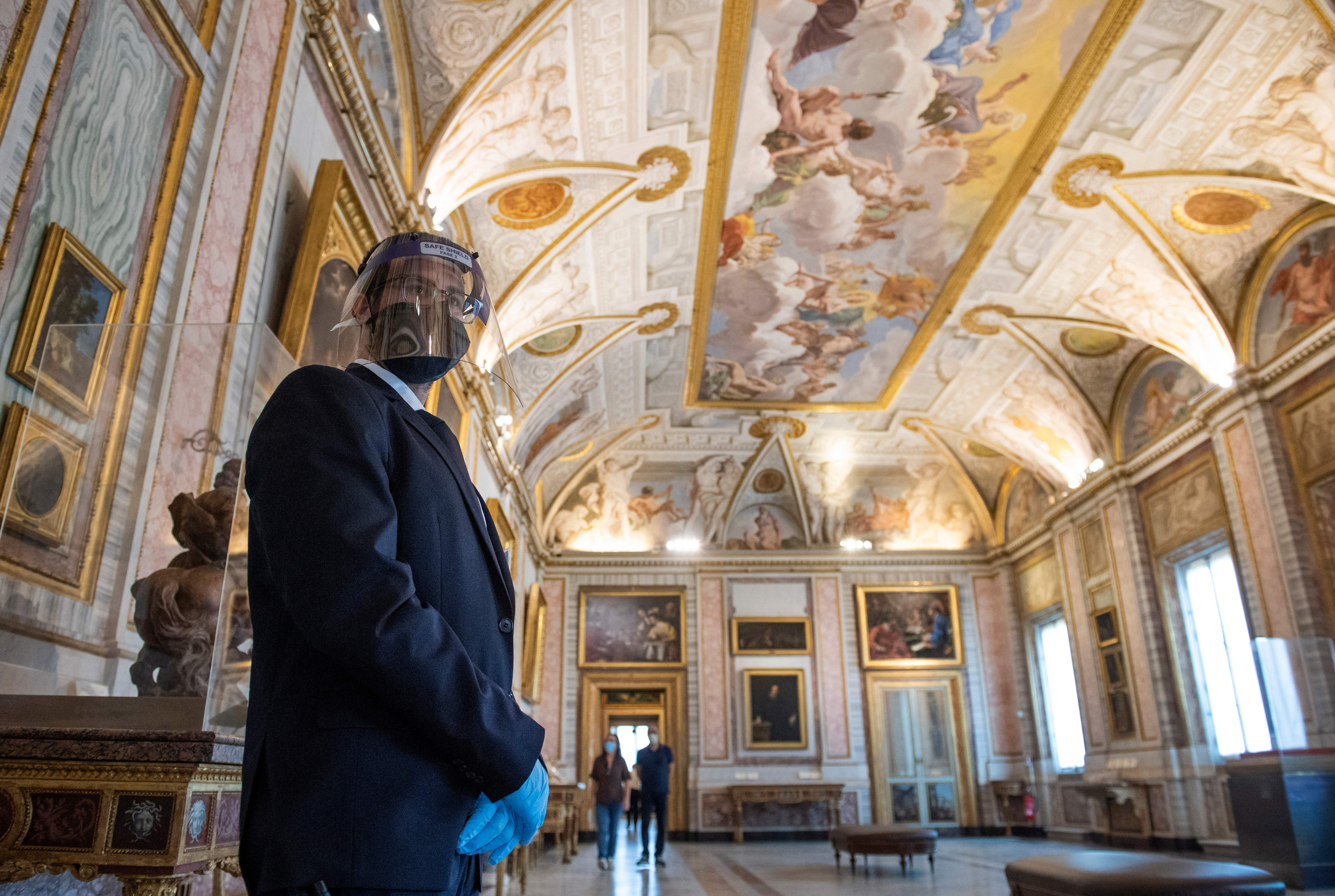 A museum attendant wearing a face mask and shield stands in a room at the Galleria Borghese museum in Rome on May 19, 2020. (Photo by TIZIANA FABI/AFP via Getty Images)