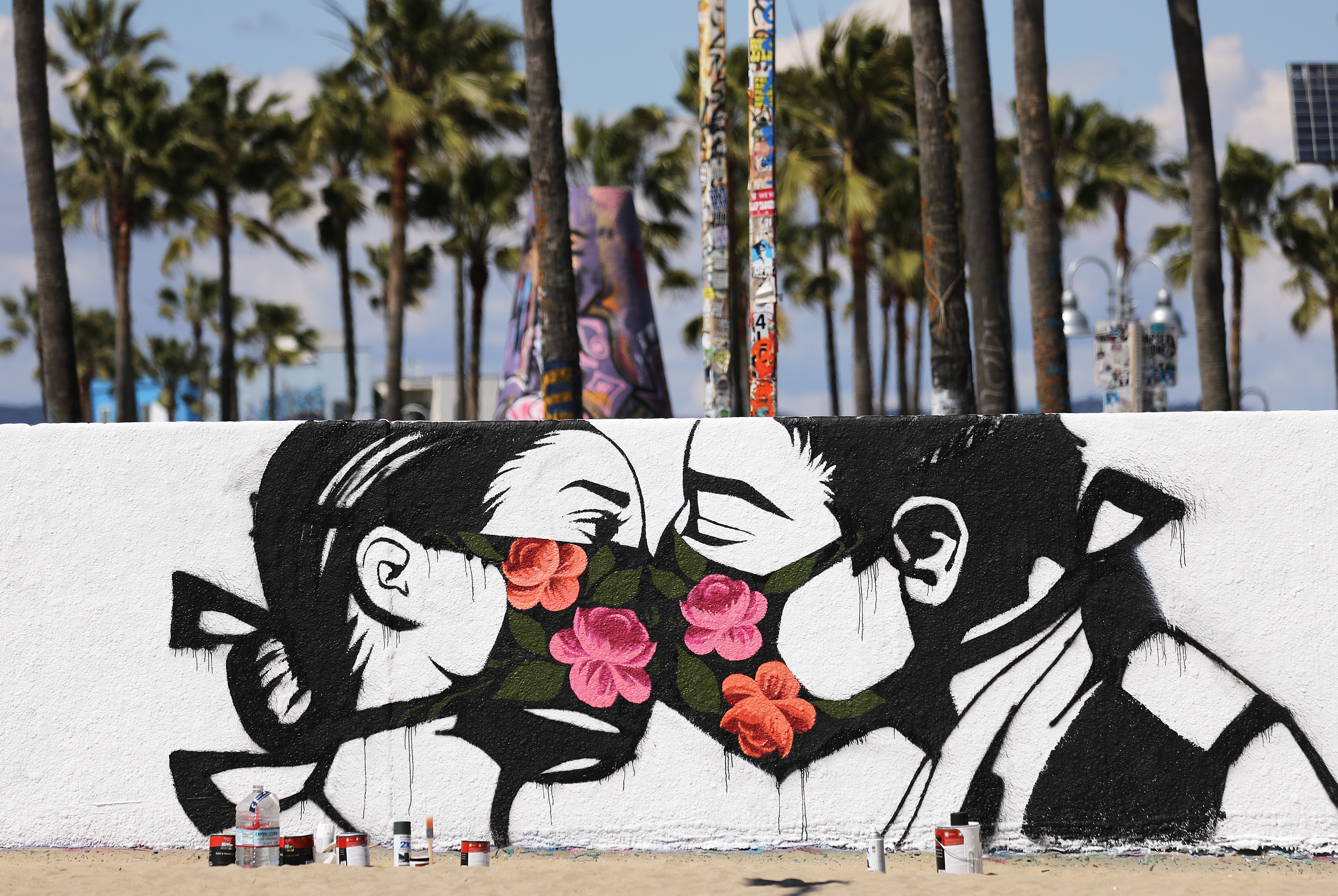 Palm trees stand behind a street art piece by artist Pony Wave depicting two people kissing while wearing face masks on Venice Beach on March 21, 2020 in Venice, California. (Photo by Mario Tama/Getty Images)