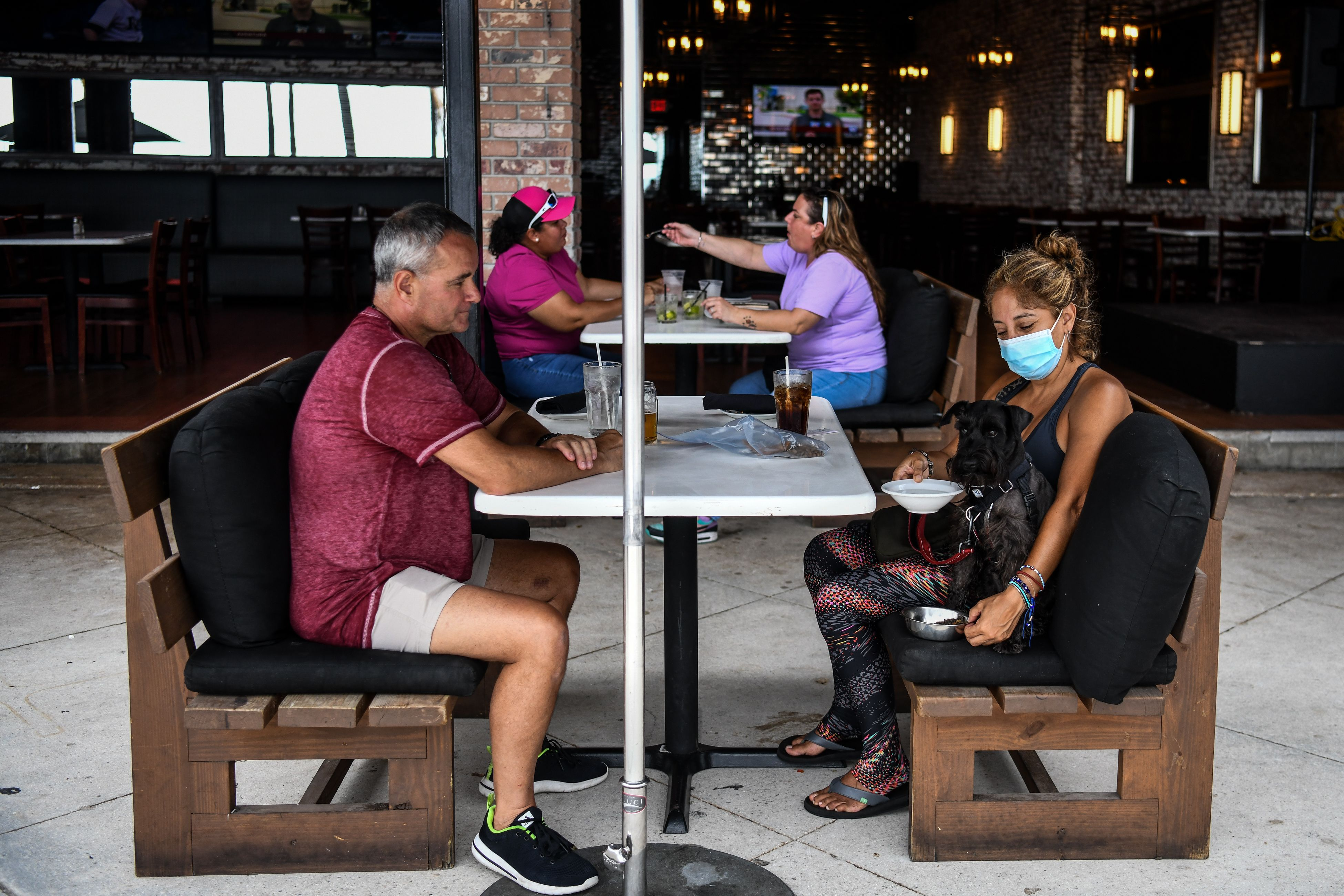 People eat sitting outside of a restaurant on Fort Lauderdale Beach Boulevard in Fort Lauderdale, Florida on May 18, 2020. (Photo by CHANDAN KHANNA/AFP via Getty Images)