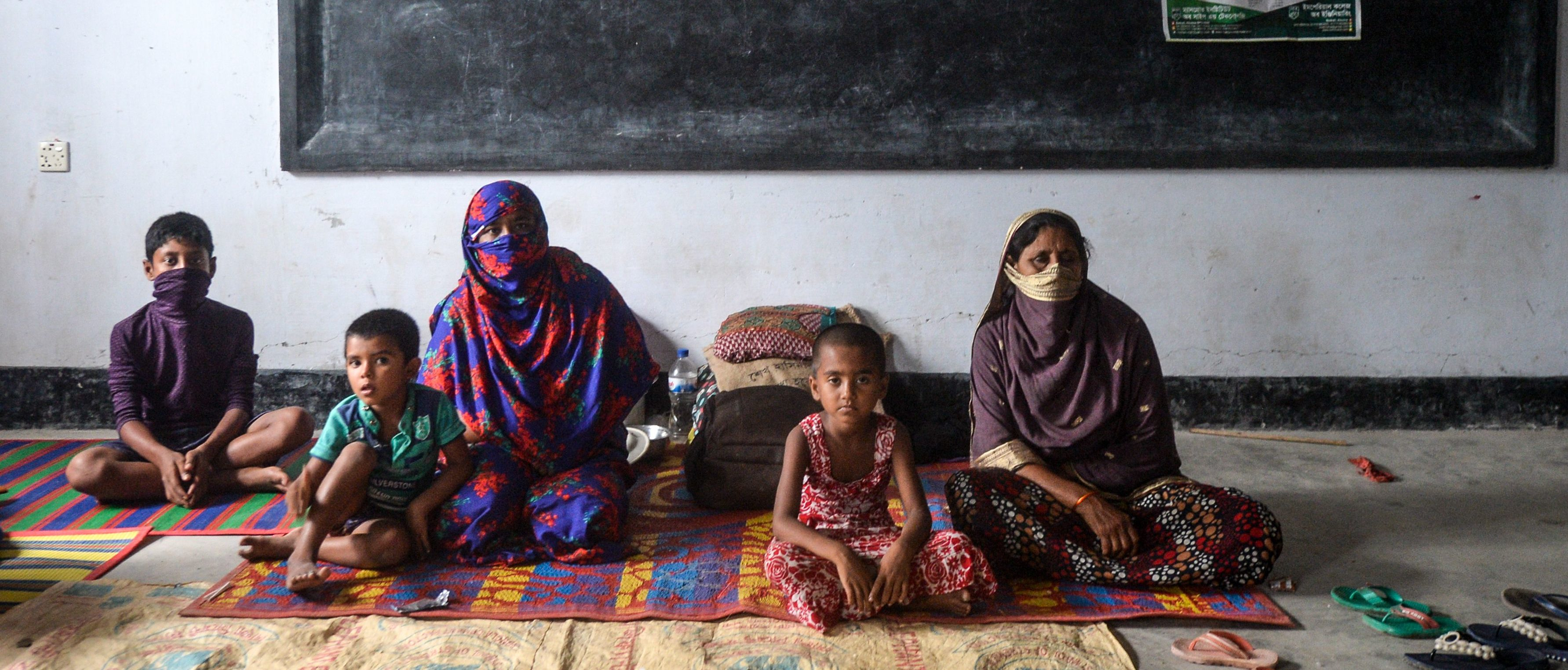 Residents rest in a shelter ahead of the expected landfall of cyclone Amphan in Dacope of Khulna district on May 20, 2020. - Several million people were taking shelter and praying for the best on Wednesday as the Bay of Bengal's fiercest cyclone in decades roared towards Bangladesh and eastern India, with forecasts of a potentially devastating and deadly storm surge. Authorities have scrambled to evacuate low lying areas in the path of Amphan, which is only the second