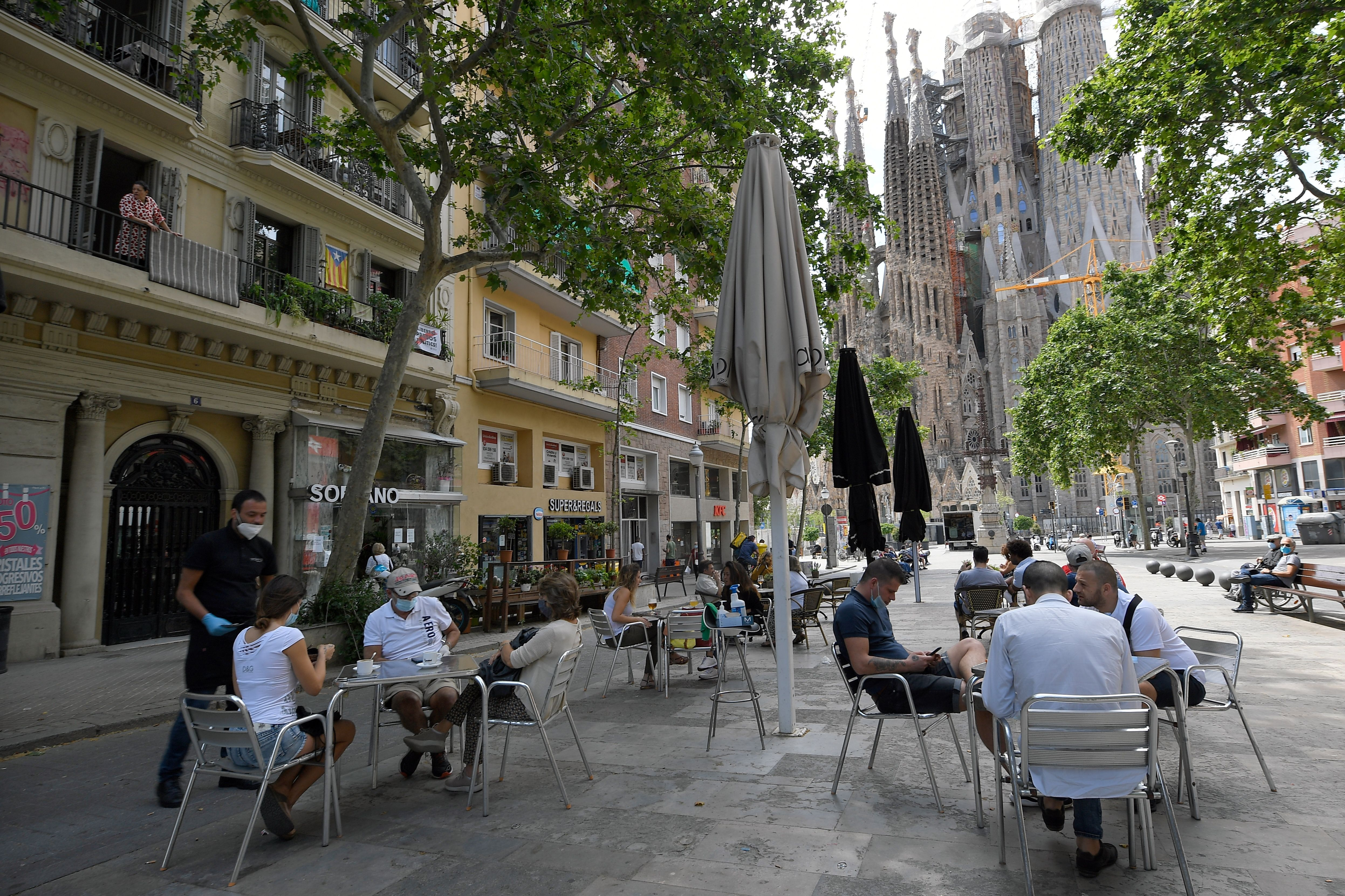People sit at a terrace bar near the Sagrada Familia on 25 May, 2020 in Barcelona. (Photo by LLUIS GENE/AFP via Getty Images)