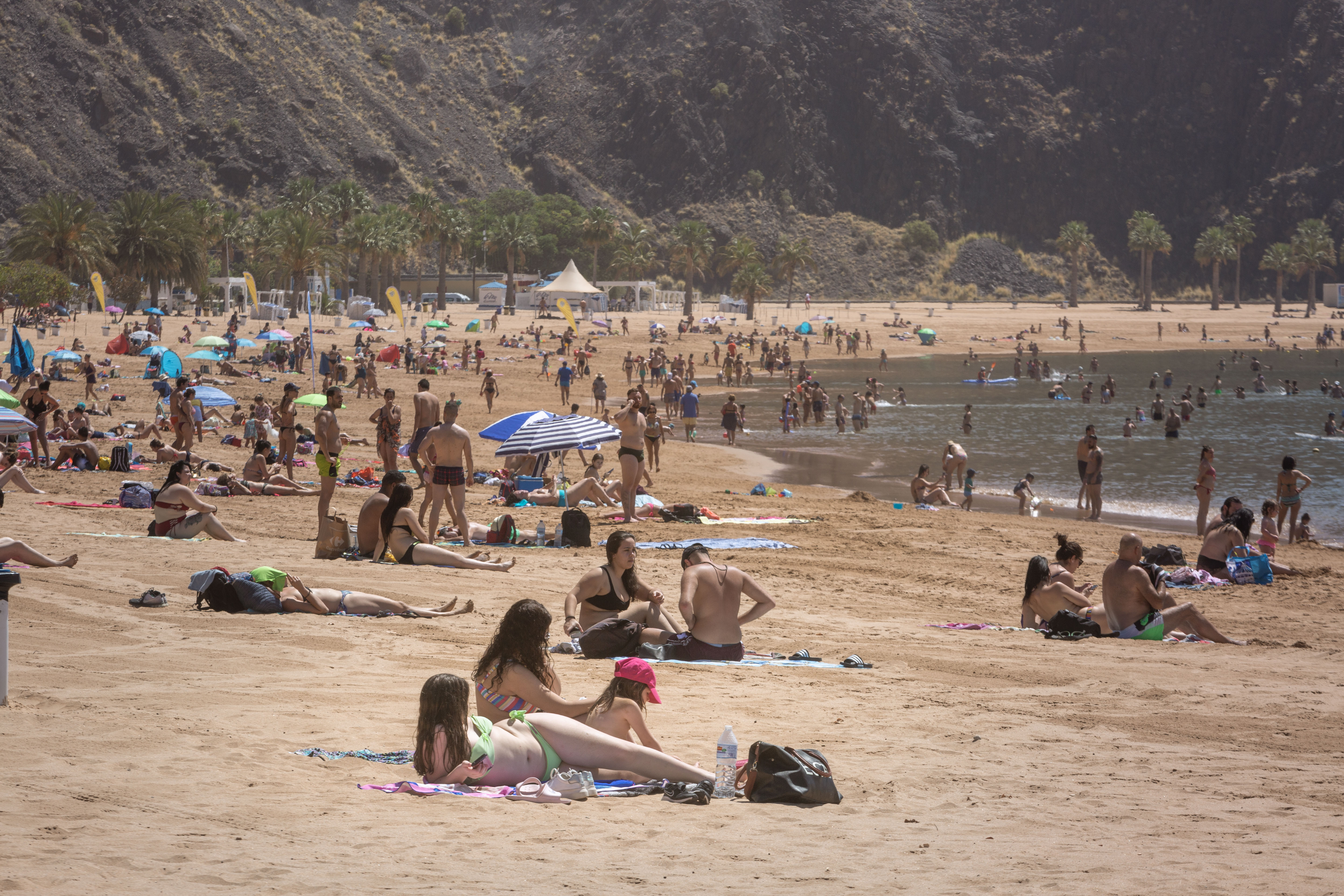 People sunbathe at Las Teresitas beach in the Spanish Canry Island of Tenerife on May 25, 2020, on the first day after beaches reopened in parts of the country after months-long closures. - Regions incorporating just under half of Spain's nearly 47 million inhabitants were moving into phase two of the three-stage rollback that is due to be completed by the end of June. (Photo by DESIREE MARTIN / AFP) (Photo by DESIREE MARTIN/AFP via Getty Images)