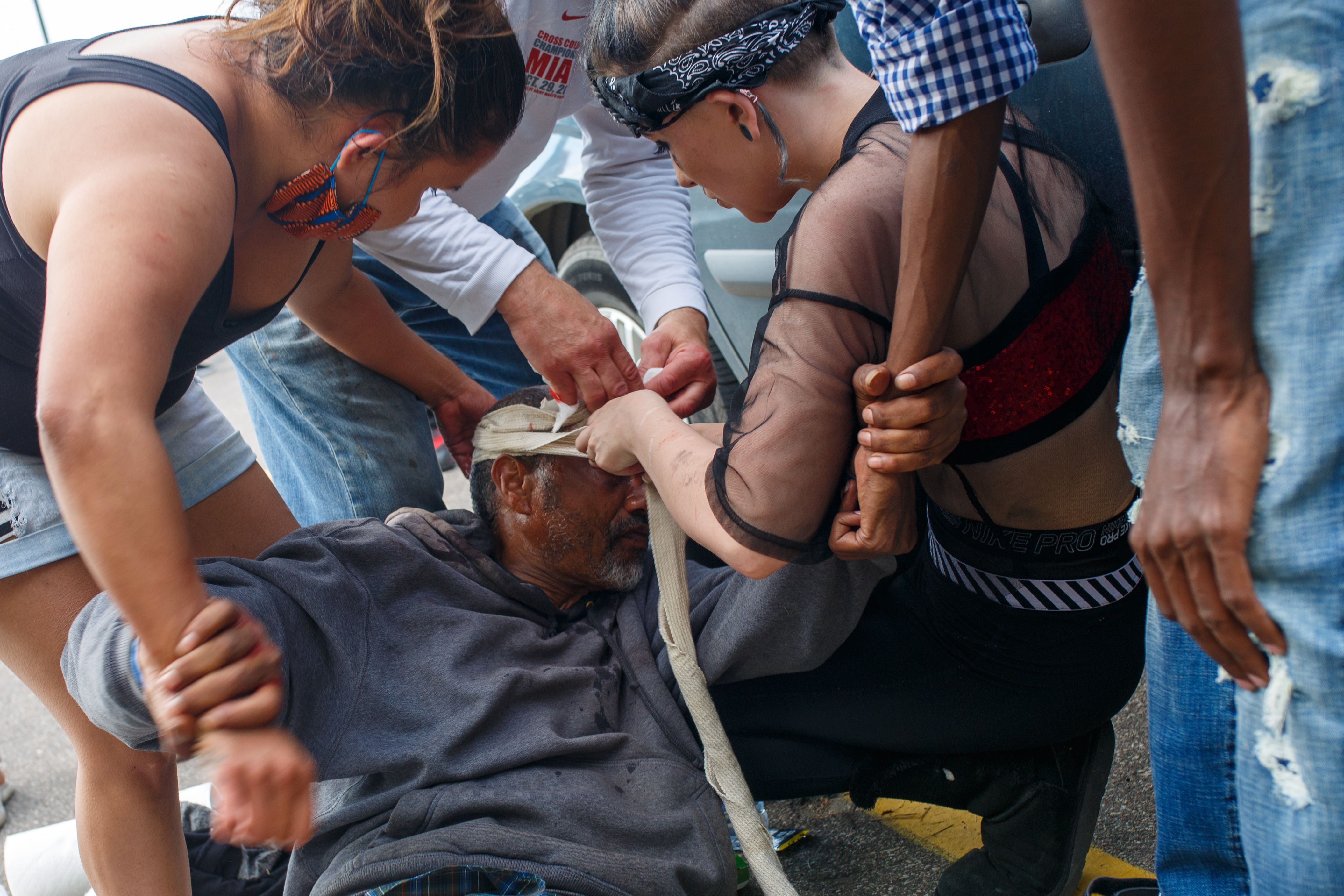 A Somali-American injured man is helped by others as protesters clash with the police during demonstrations against the death of George Floyd outside the 3rd Precinct Police Precinct on May 27, 2020 in Minneapolis, Minnesota. (KEREM YUCEL/AFP via Getty Images)