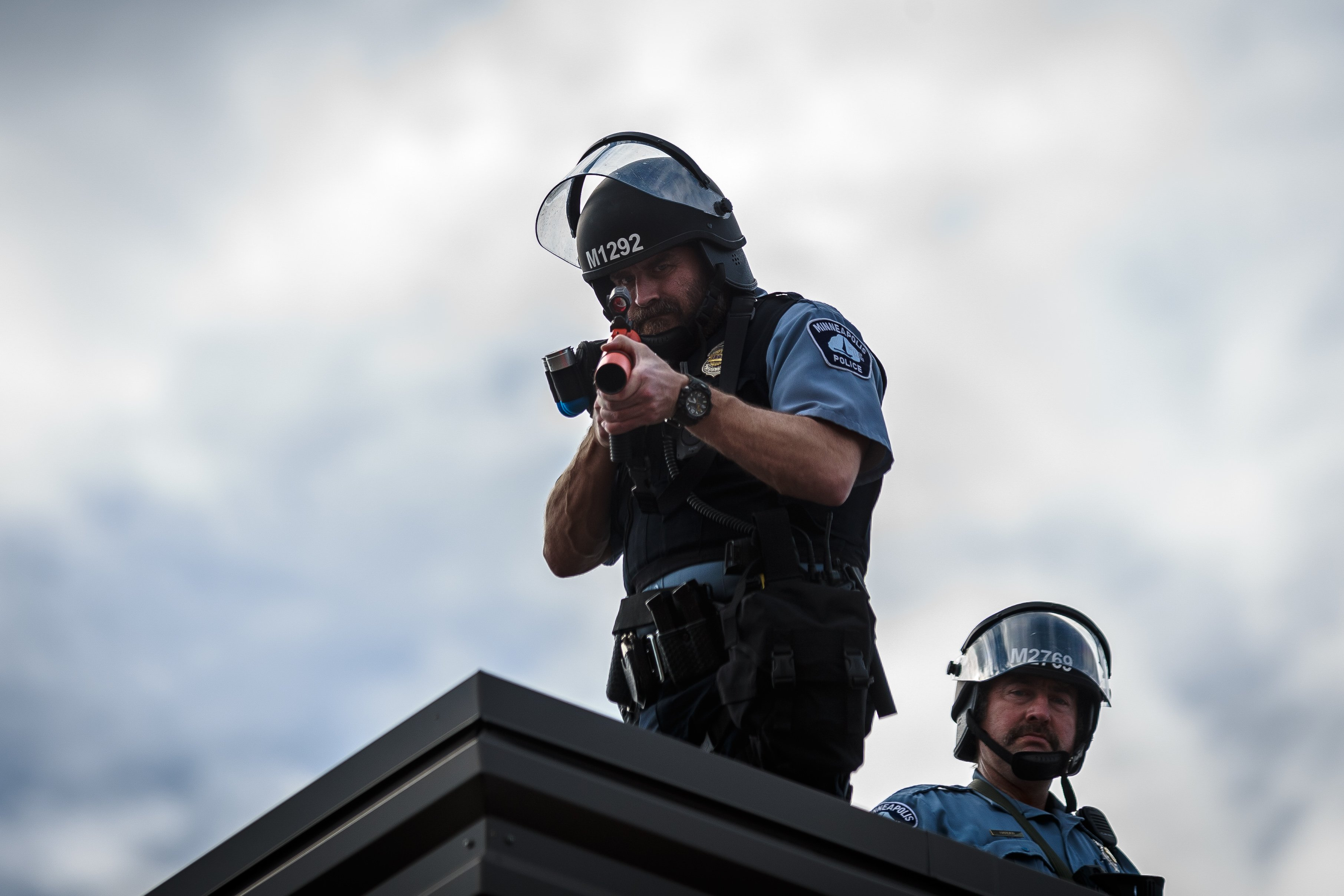 Two police officers stand on the roof of the Third Police Precinct holding a projectile launcher during a demonstration in a call for justice for George Floyd following his death, outside the 3rd Police Precinct on May 27, 2020 in Minneapolis, Minnesota. (KEREM YUCEL/AFP via Getty Images)