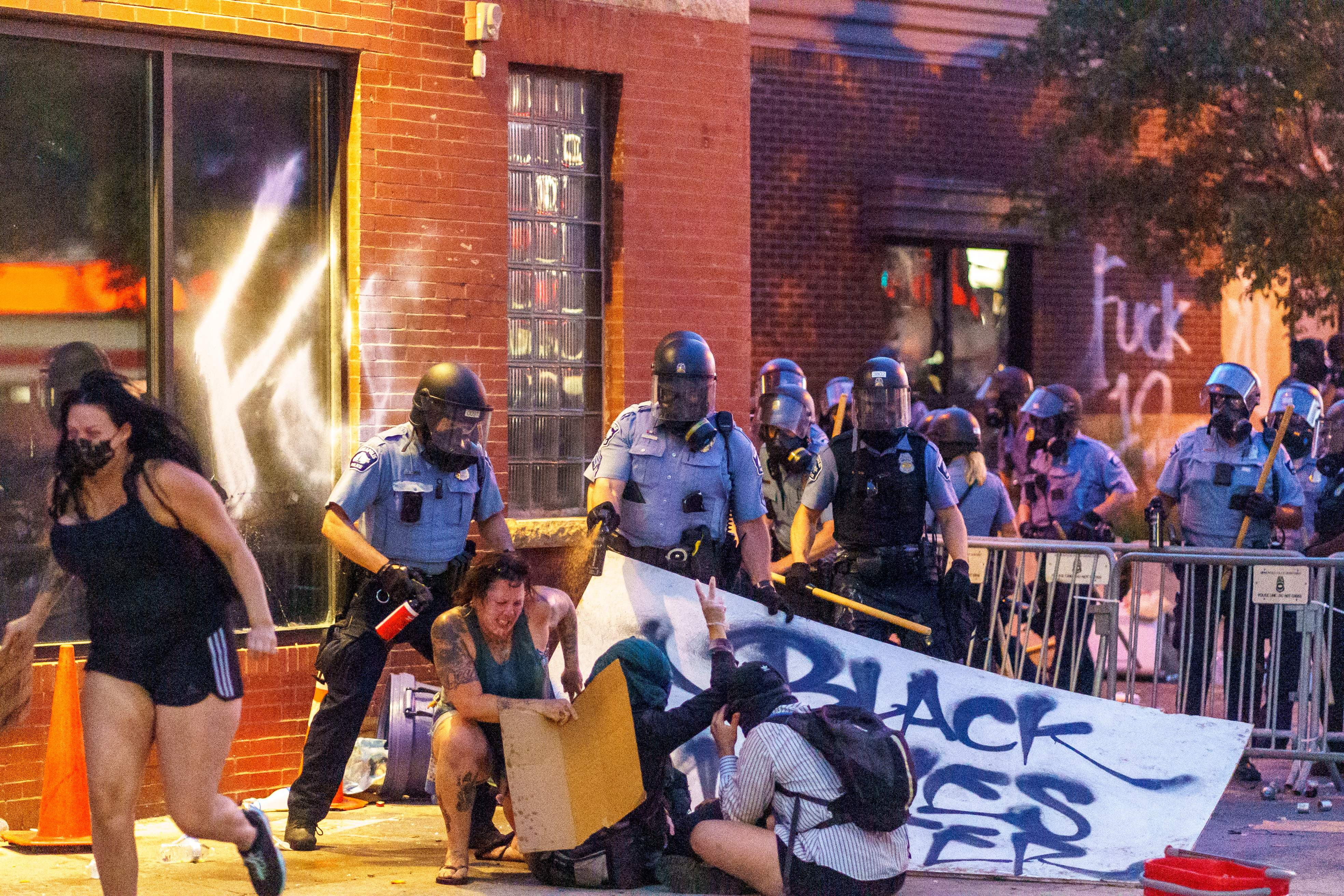Police spray protesters with pepper spray during a demonstration over the killing of George Floyd by a policeman outside the Third Police Precinct on May 27, 2020 in Minneapolis, Minnesota. (KEREM YUCEL/AFP via Getty Images)