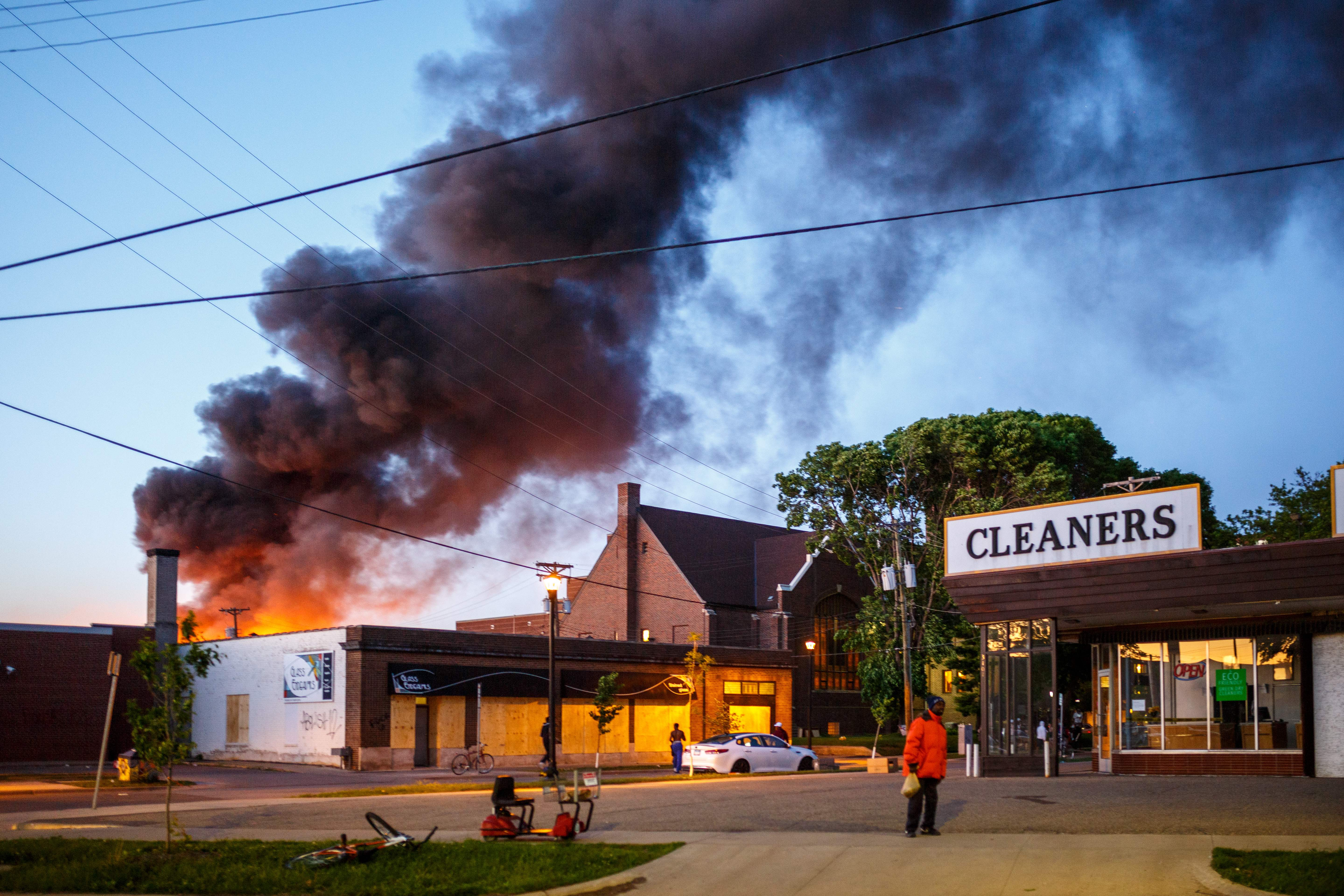 Flames rise from the cleaners shoop near the Third Police Precinct on May 28, 2020 in Minneapolis, Minnesota, during a protest over the death of George Floyd.(Photo by KEREM YUCEL/AFP via Getty Images)
