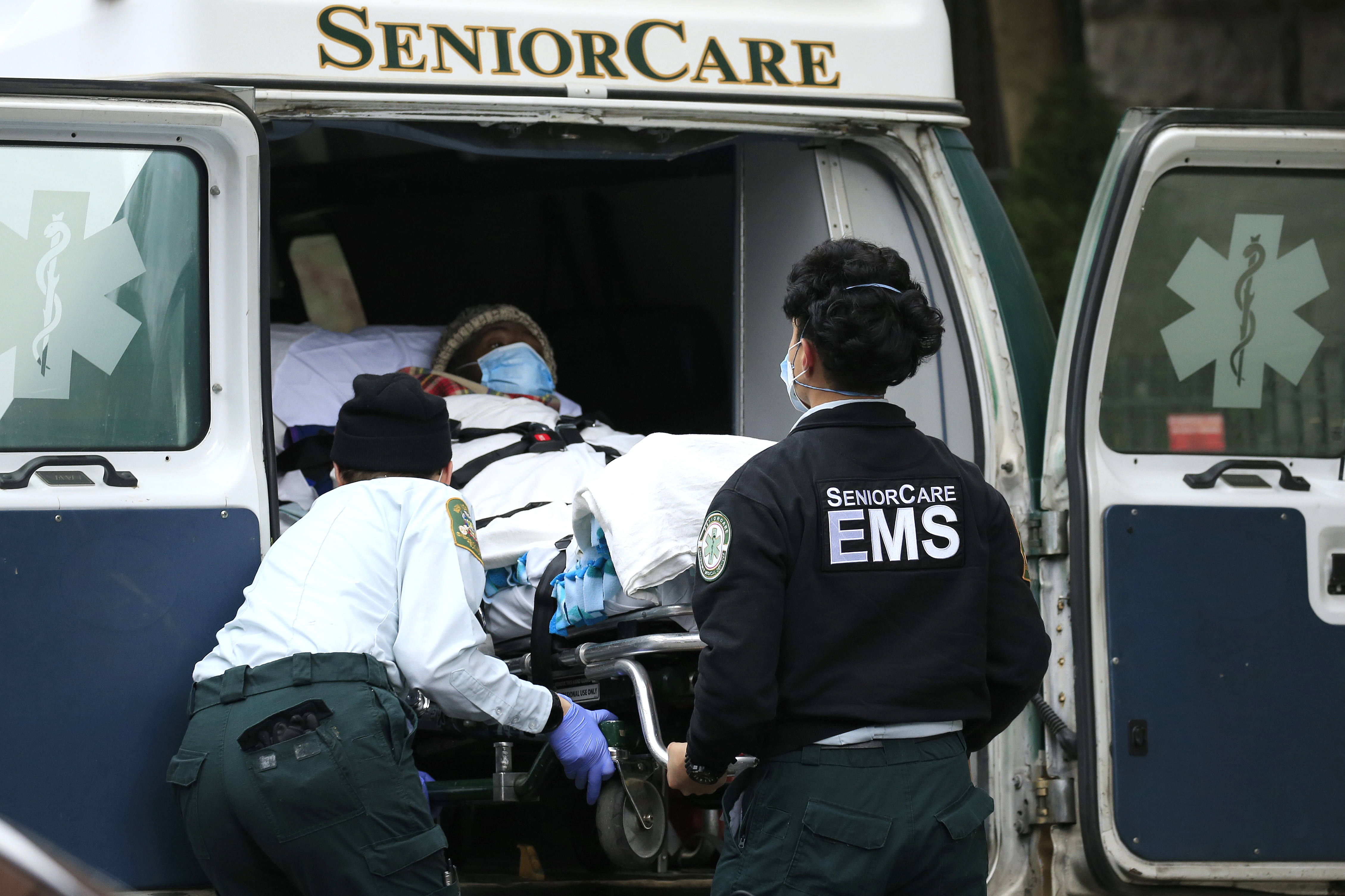 Emergency Medical Service workers unload a patient out of their ambulance at the Cobble Hill Health Center on April 18, 2020 in the Cobble Hill neighborhood of the Brooklyn borough of New York City. (Photo by Justin Heiman/Getty Images)
