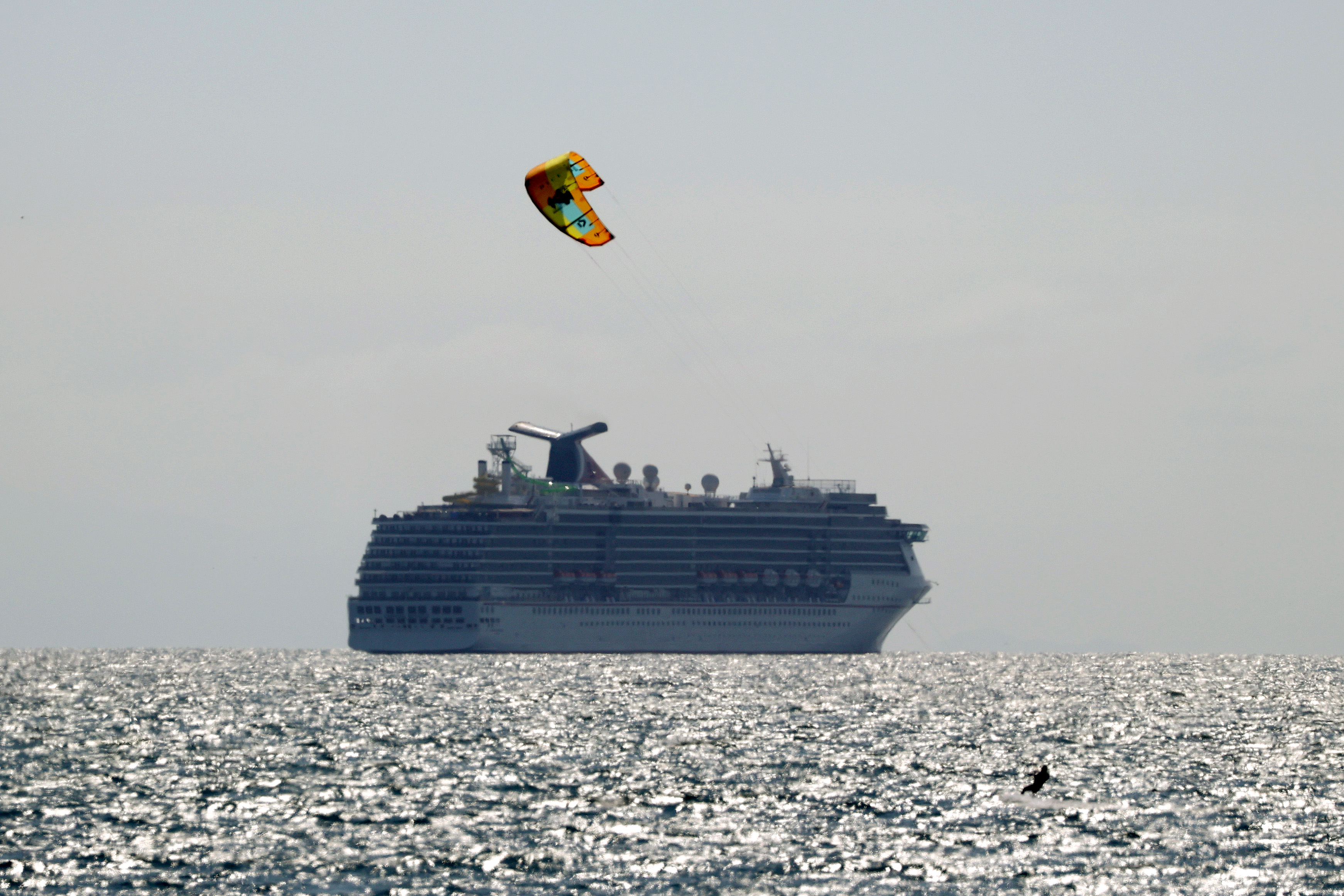 A kite surfer passes in front of an anchored Carnival cruise ship on April 20, 2020 in Huntington Beach, California. (Photo by Michael Heiman/Getty Images)