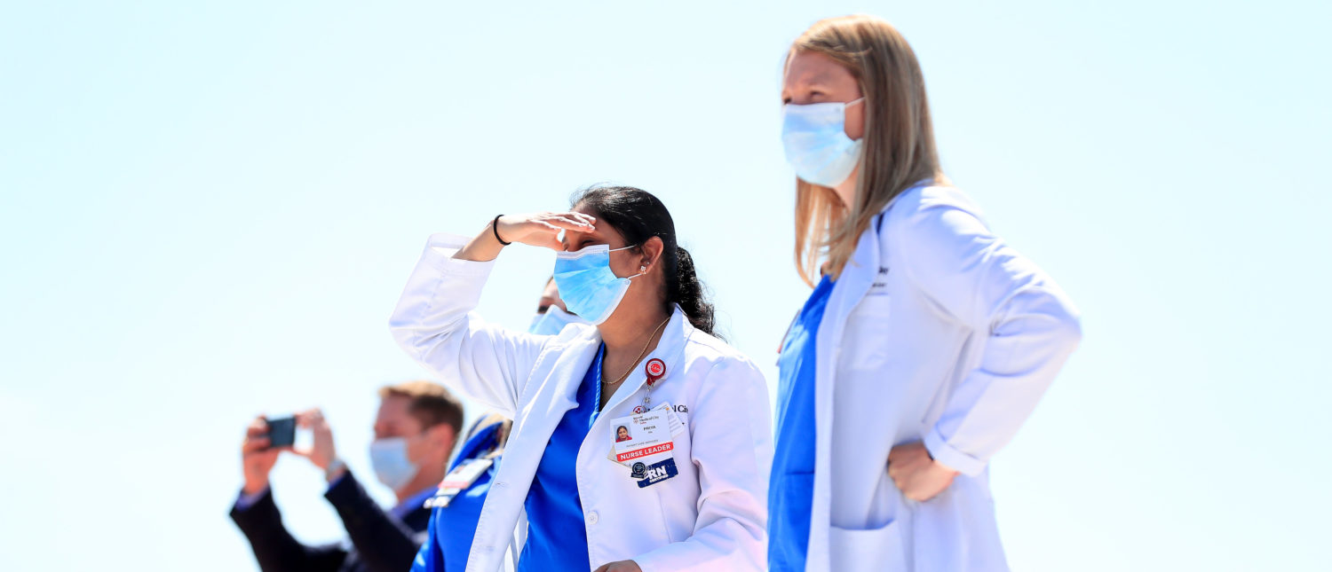DALLAS, TEXAS - MAY 06: Hospital staff, including nurses, doctors and administrators, look on in anticipation of the United States Navy Blue Angels flyover above Medical City Dallas on May 06, 2020 in Dallas, Texas. The flyover across the Dallas-Fort Worth area was conducted as a show of support for health care workers and first responders fighting the coronavirus (COVID-19) pandemic. (Photo by Tom Pennington/Getty Images)