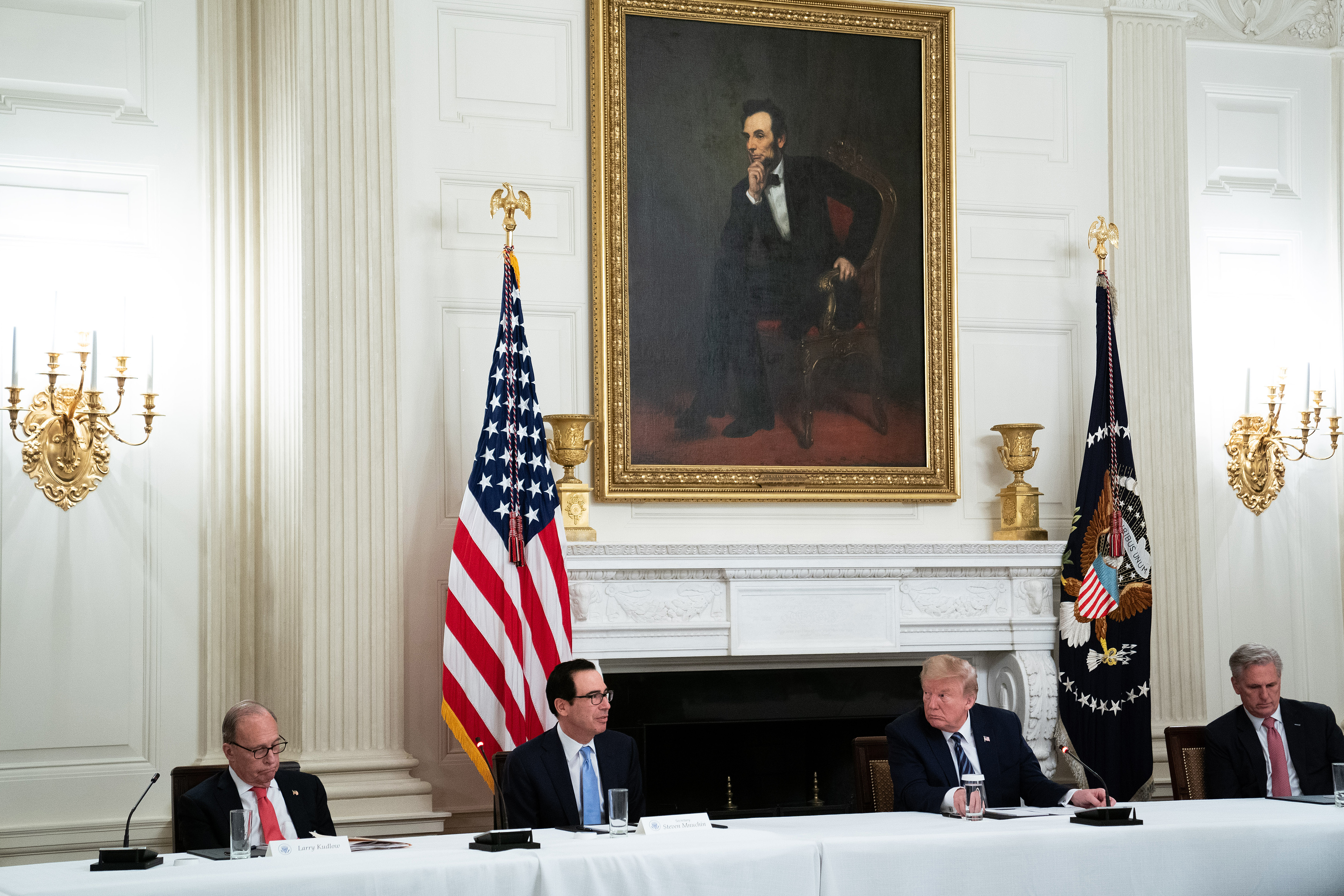 """WASHINGTON, DC - MAY 08: (L-R) White House Economic Council Director Larry Kudlow, Treasury Secretary Steven Mnuchin, President Donald Trump and House Minority Leader Kevin McCarthy (R-CA) meet with Congressional Republicans in the State Dining Room at the White House May 08, 2020 in Washington, DC. Trump insisted that the national economy will recover this year from the damage caused by novel coronavirus pandemic, saying, """"I'm calling it the transition to greatness."""" (Photo by Anna Moneymaker-Pool/Getty Images)"""