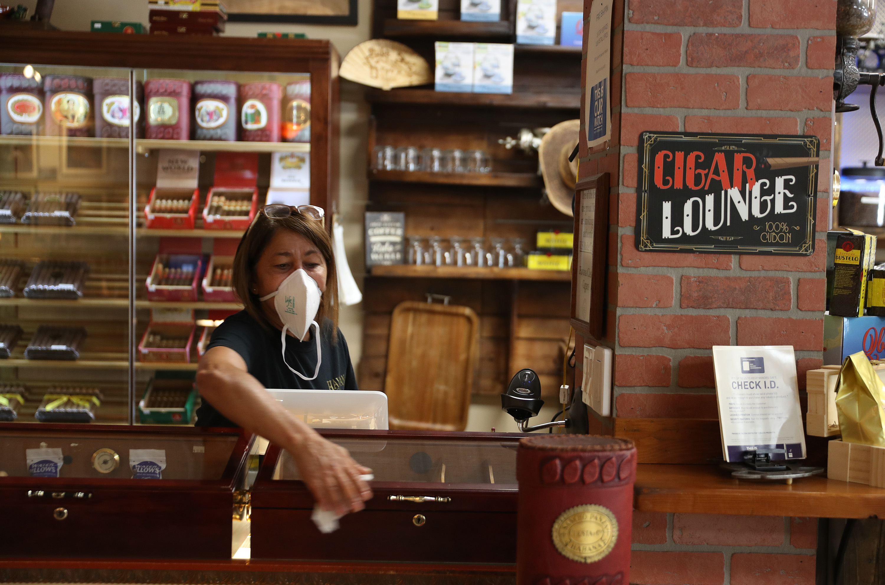 Vilma Perez uses sanitizer wipes to wipe down a counter as she helps prepare to open the Havana Classic cigar shop on May 19, 2020 in Miami, Florida. (Photo by Joe Raedle/Getty Images)