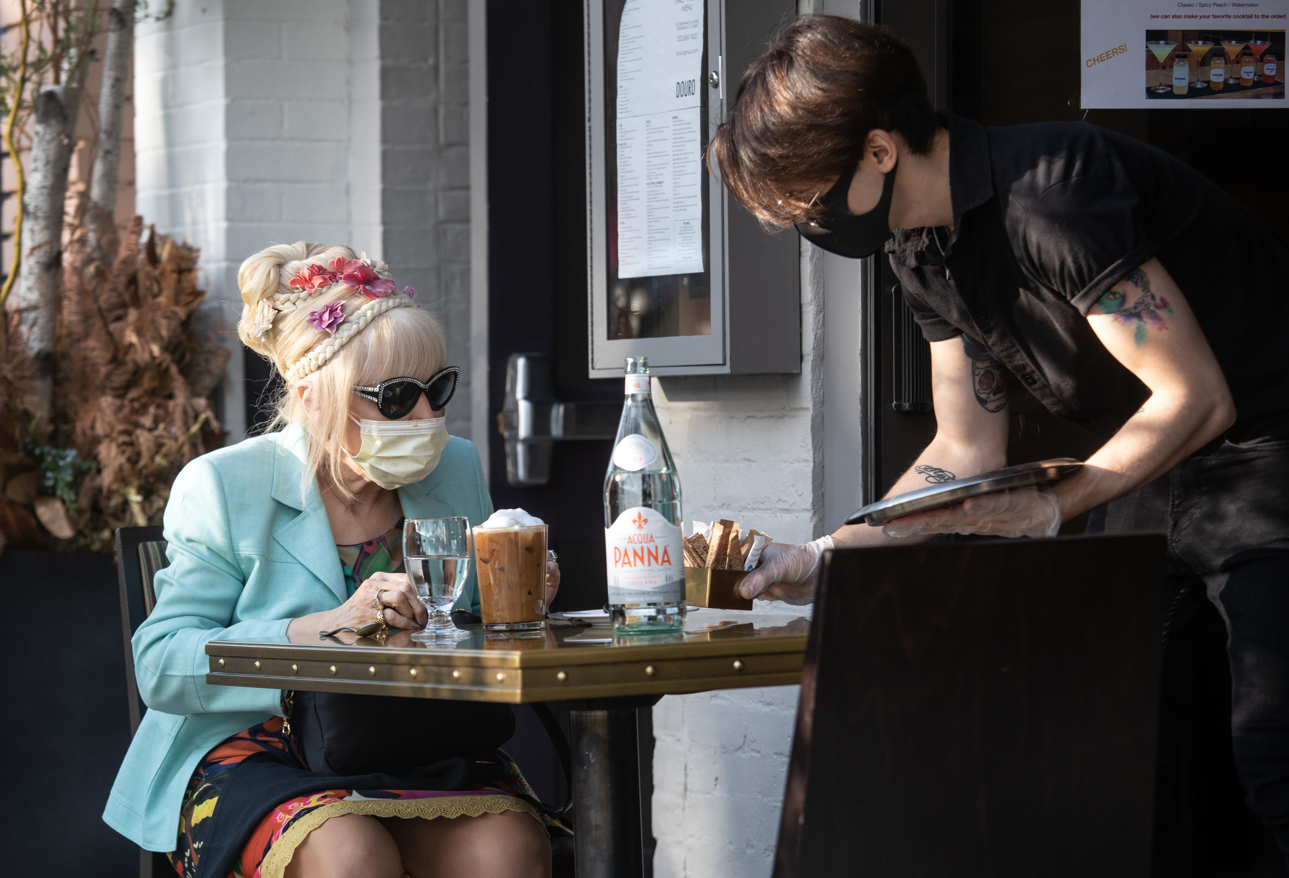 A server brings out sweetener to patron Francesca Macartney Beale at Douro restaurant on May 20, 2020 in Greenwich, Connecticut. (Photo by John Moore/Getty Images)