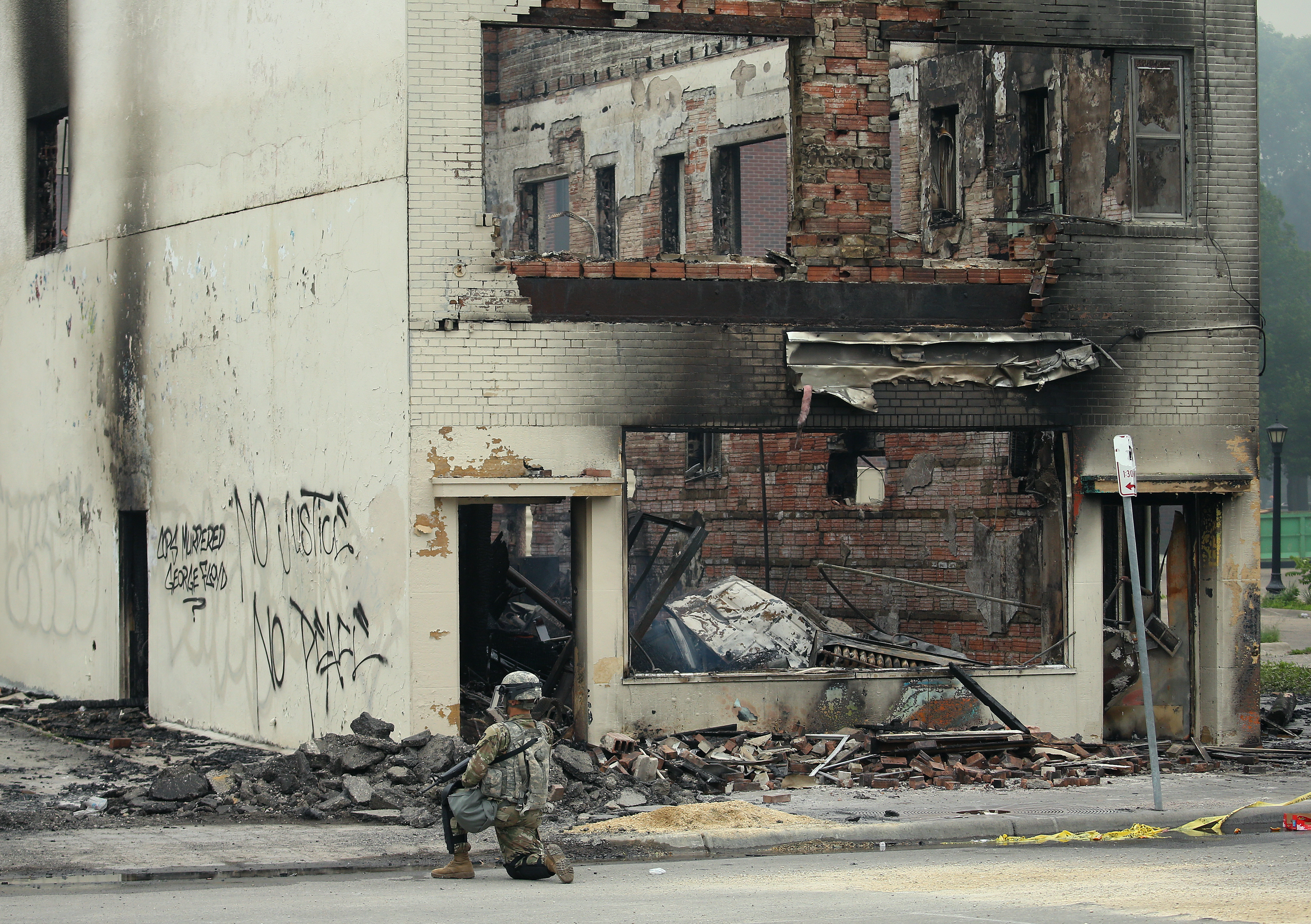 MINNEAPOLIS, MINNESOTA - MAY 28: A member of the National Guard patrols near a burned out building on the fourth day of protests on May 29, 2020 in Minneapolis, Minnesota. The National Guard has been activated as protests continue after the death of George Floyd which has caused widespread destruction and fires across Minneapolis and St. Paul. (Photo by Scott Olson/Getty Images)
