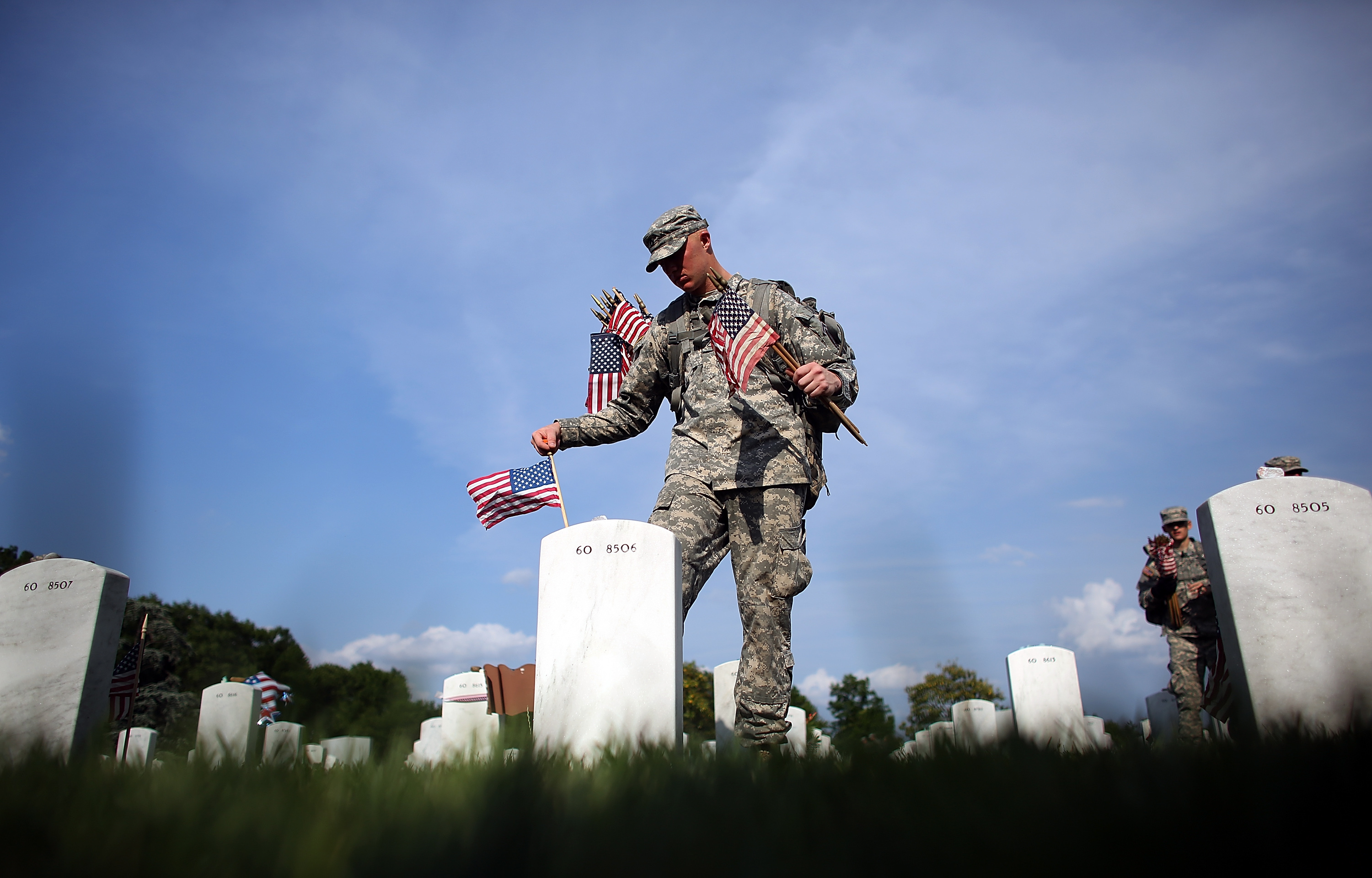 Members of the 3rd U.S. Infantry Regiment place American flags at the graves of U.S. soldiers buried in Section 60 at Arlington National Cemetery in preparation for Memorial Day May 24, 2012 in Arlington, Virginia. (Photo by Win McNamee/Getty Images)
