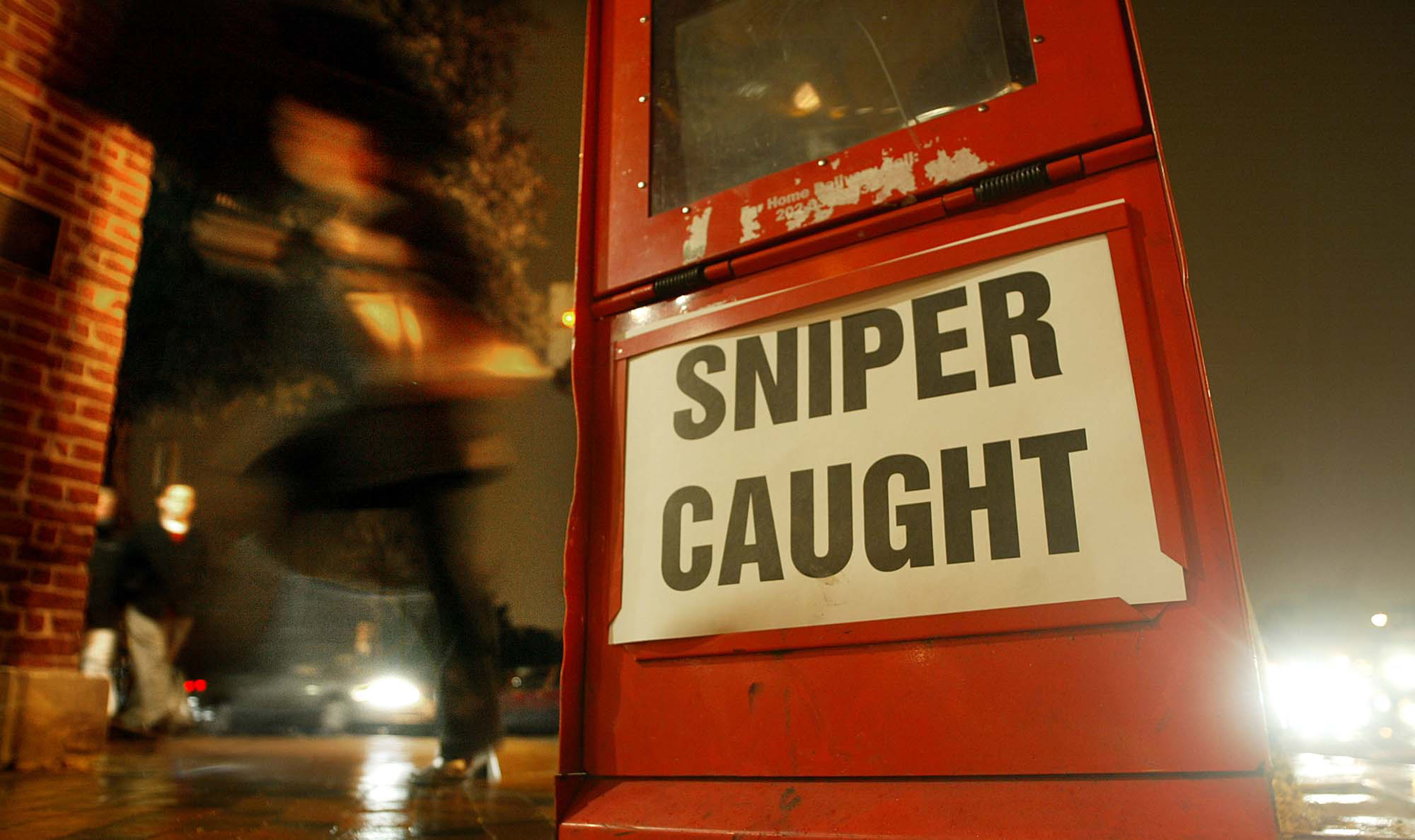 "A newspaper box headline reading ""Sniper Caught"" is seen on a Georgetown street a day after suspects John Allen Muhammad and John Lee Malvo were arrested October 25, 2002 in Washington, DC. (Photo by Mario Tama/Getty Images)"