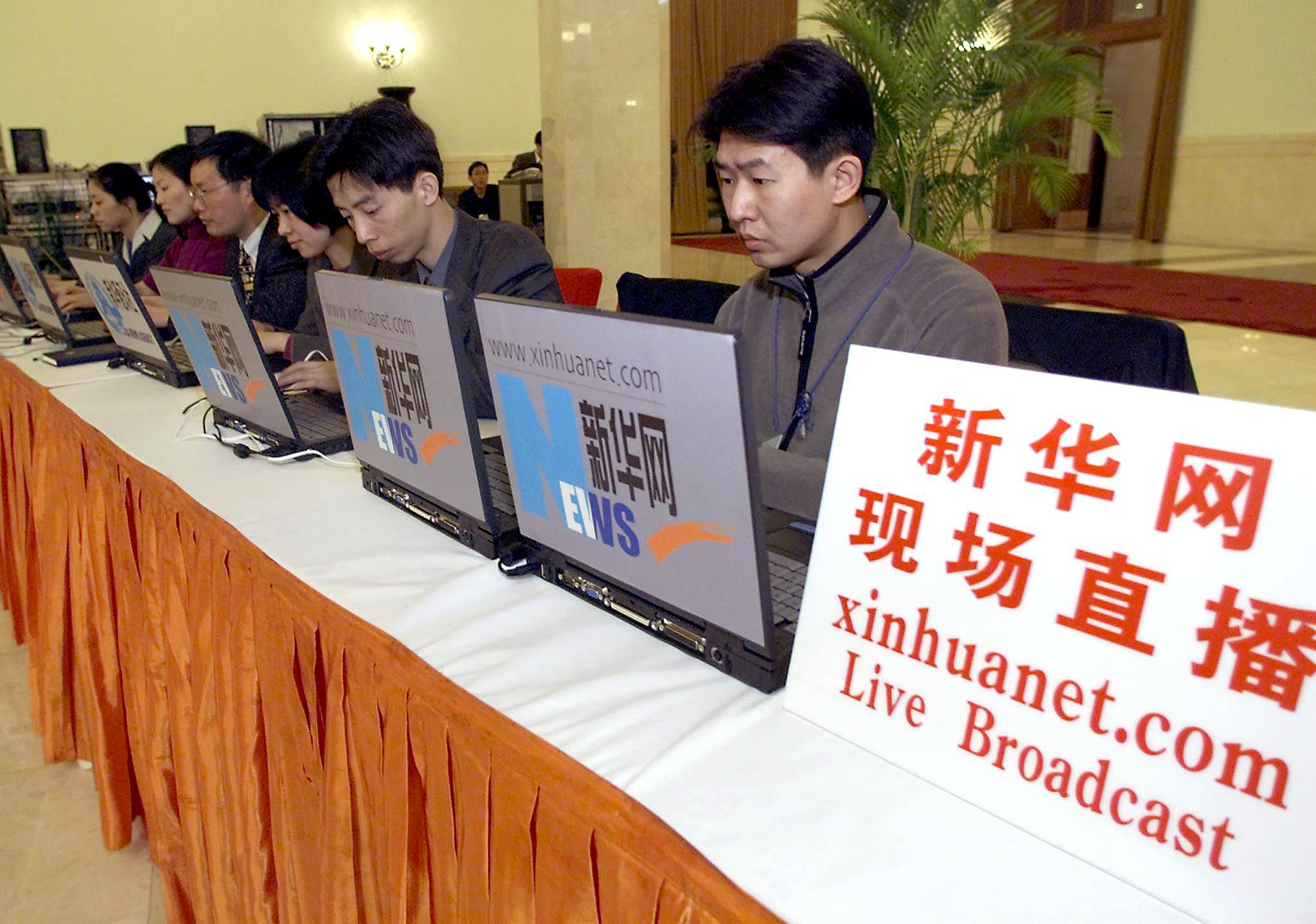 Journalists from China's official news agency Xinhua report directly from the National People's Congress at the Great Hall of the People in Beijing 06 March 2001, to their website. (GOH CHAI HIN/AFP via Getty Images)