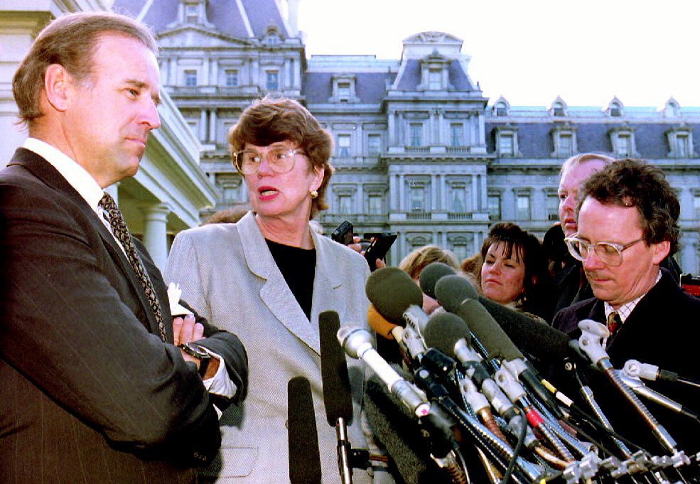 U.S. Attorney General Janet Reno (C), turns to answer a question from a reporter as she and Sen. Joseph Biden (L), D-Del, leave the White House after meeting with U.S. President Bill Clinton, 12 March 1993. (J.DAVID AKE/AFP via Getty Images)