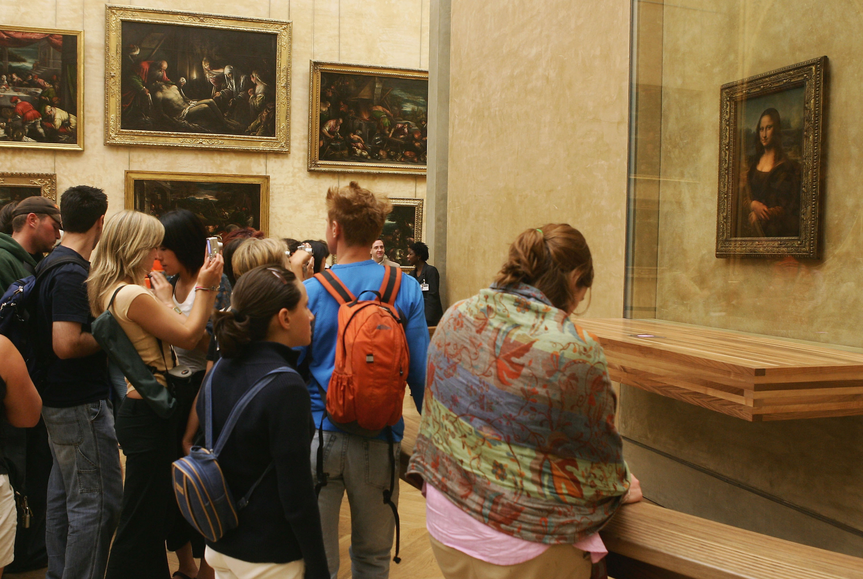 """Tourists admire the famous Leonardo Da Vinci painting """" The Mona Lisa"""" in the Grande Galerie of the Louvre museum on August 24, 2005 in Paris, France. (Photo by Pascal Le Segretain/Getty Images)"""