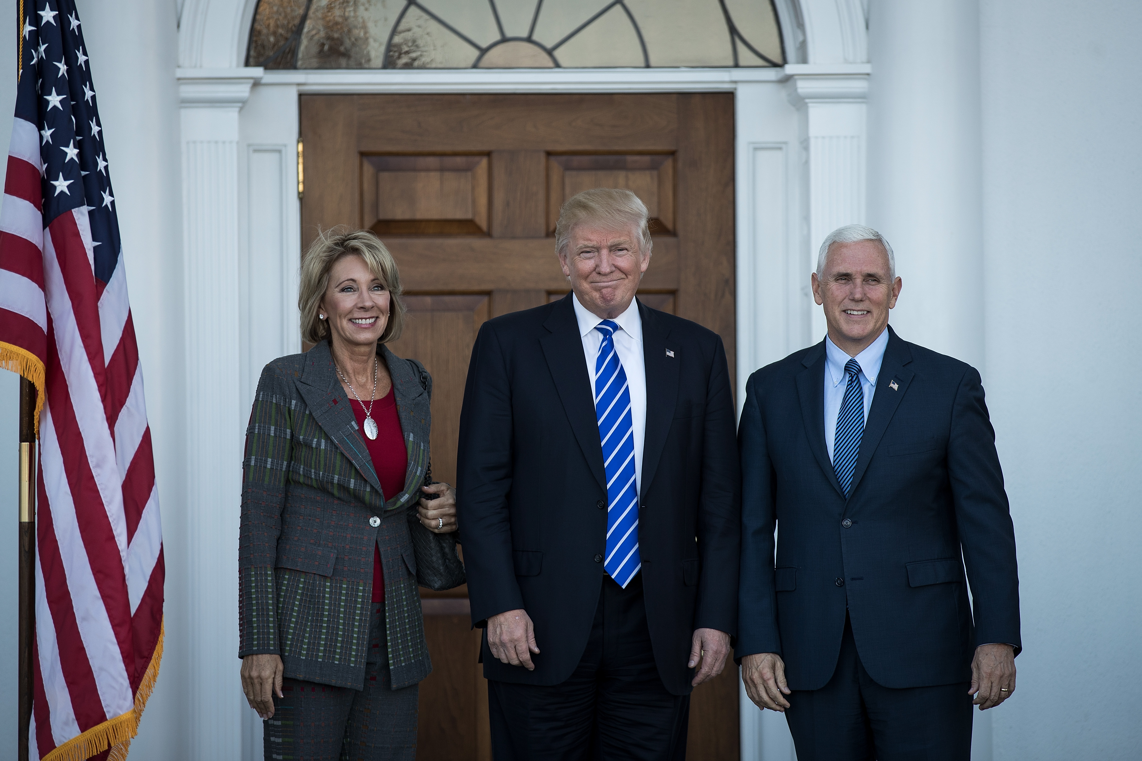 BEDMINSTER TOWNSHIP, NJ - NOVEMBER 19: (L to R) Betsy DeVos, president-elect Donald Trump and vice president-elect Mike Pence pose for a photo outside the clubhouse at Trump International Golf Club, November 19, 2016 in Bedminster Township, New Jersey. Trump and his transition team are in the process of filling cabinet and other high level positions for the new administration. (Photo by Drew Angerer/Getty Images)