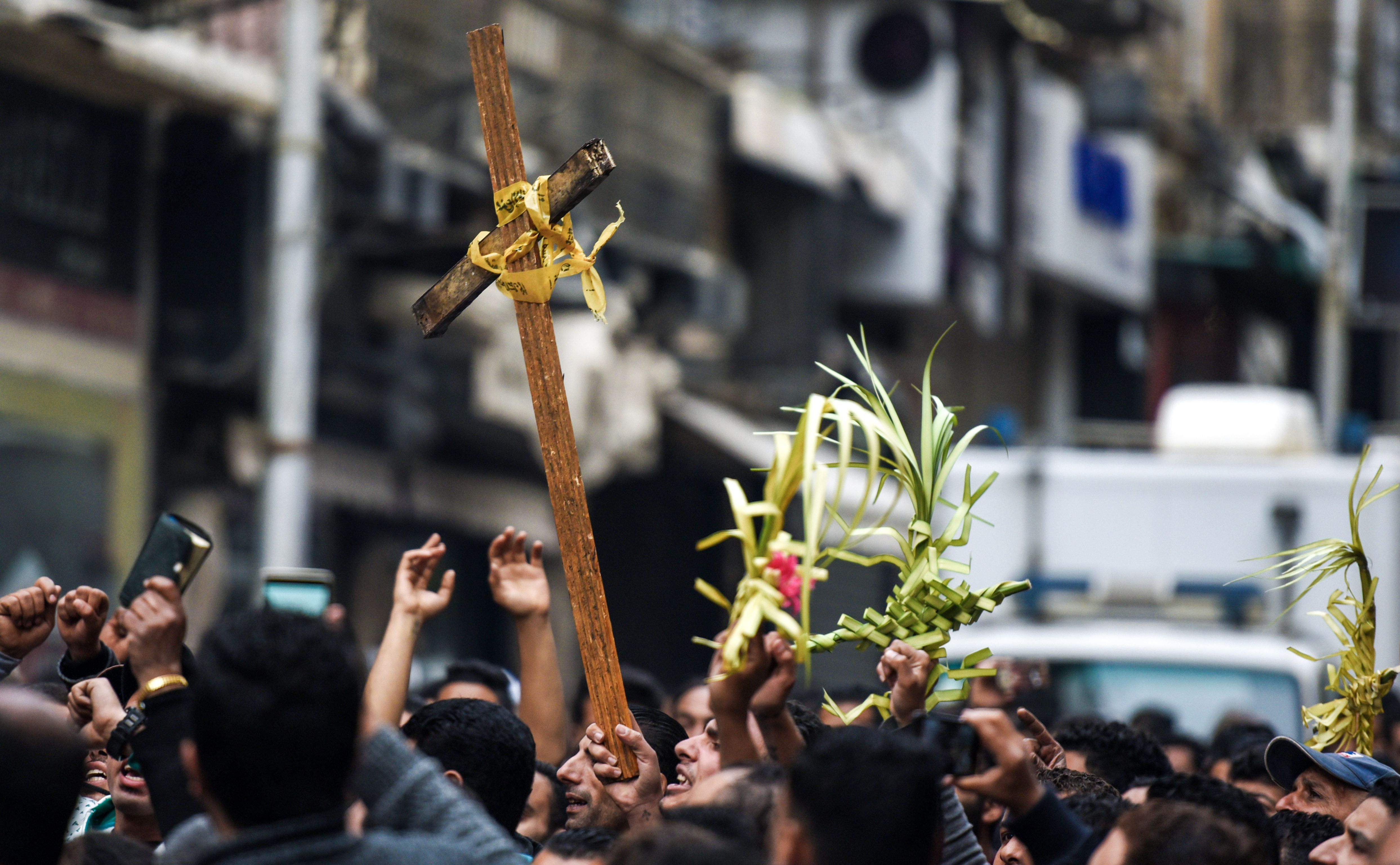 Egyptians raise a wooden cross and palm leaves originally intended for Palm Sunday celebrations, as they gather outside the Coptic Orthodox Patriarchate in Alexandria after a bomb blast struck outside as worshippers attended Palm Sunday mass on April 9, 2017. (MOHAMED EL-SHAHED/AFP via Getty Images)