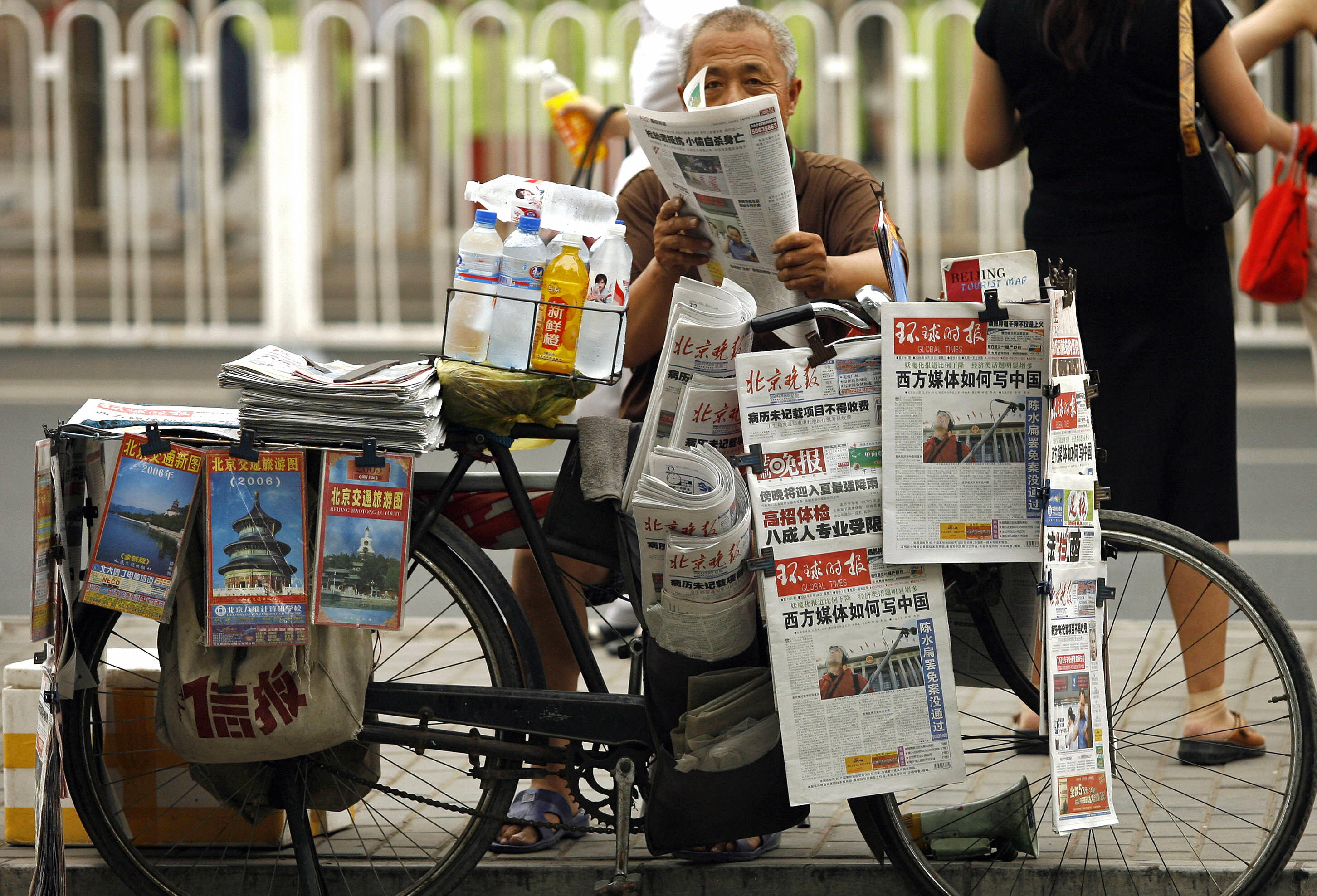 A newspaper vendor sells from his bicycle on a street in Beijing, 28 June 2006. (PETER PARKS/AFP via Getty Images)