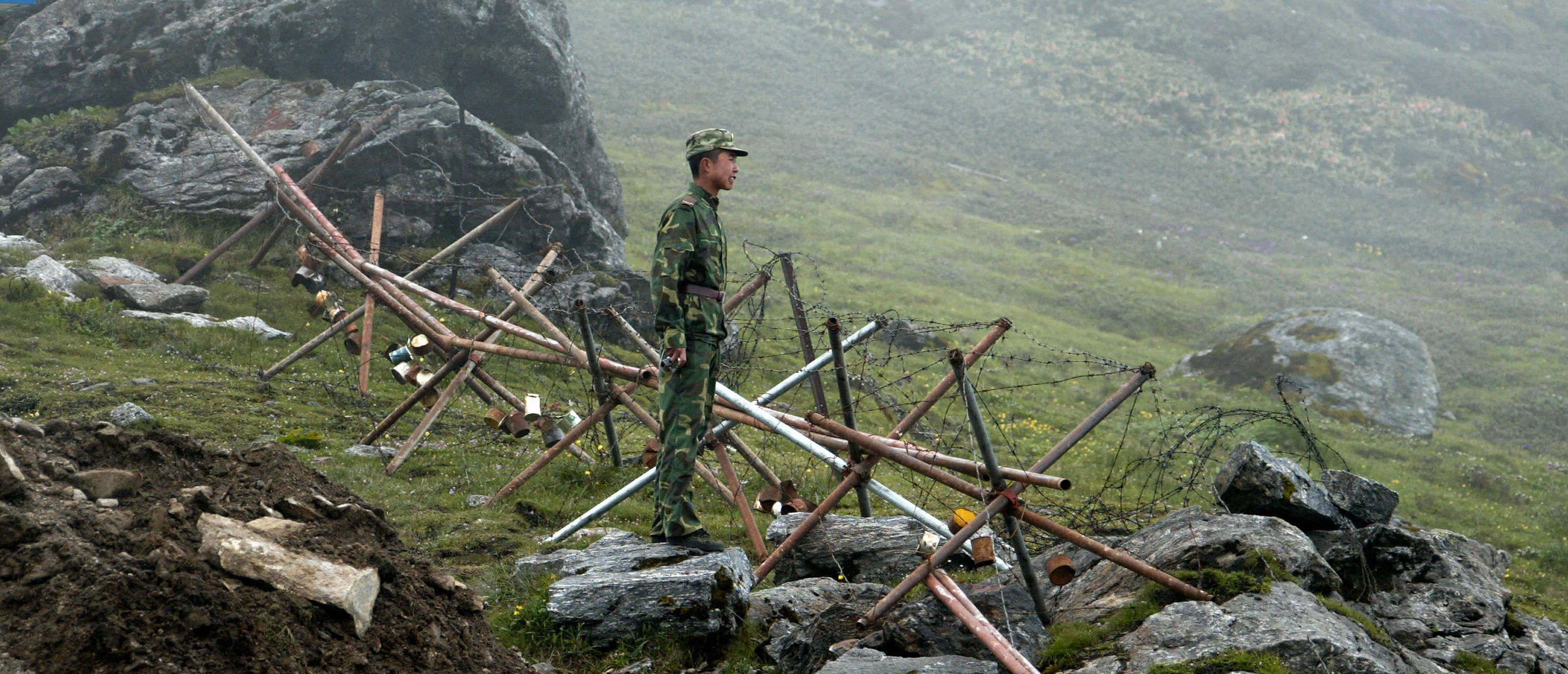 In this photograph taken on July 10, 2008, a Chinese soldier stands guard on the Chinese side of the ancient Nathu La border crossing between India and China. When the two Asian giants opened the 4,500-metre-high (15,000 feet) pass in 2006 to improve ties dogged by a bitter war in 1962 that saw the route closed for 44 years, many on both sides hoped it would boost trade. Two years on, optimism has given way to despair as the flow of traders has shrunk to a trickle because of red tape, poor facilities and sub-standard roads in India's remote northeastern mountainous state of Sikkim. AFP PHOTO/Diptendu DUTTA (Photo credit should read DIPTENDU DUTTA/AFP via Getty Images)