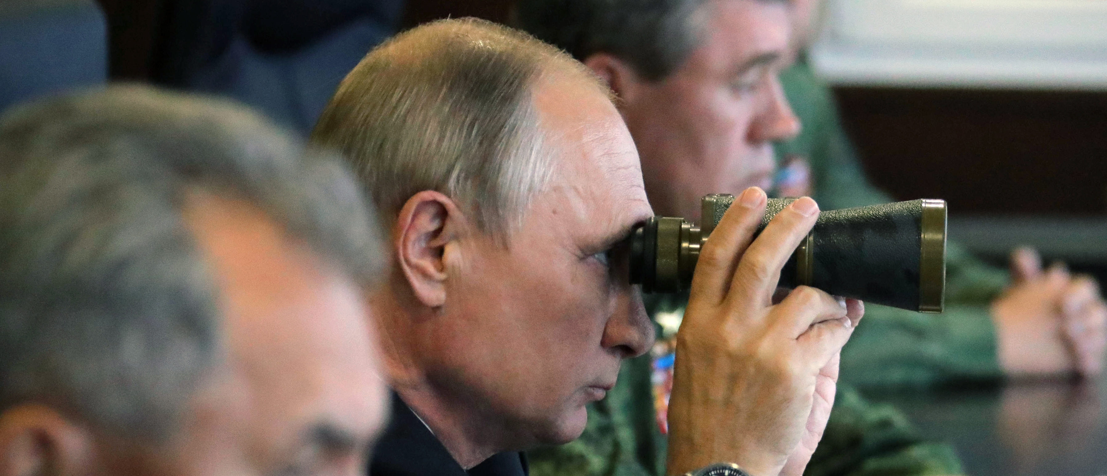 TOPSHOT - Russian President Vladimir Putin (C), accompanied by Defence Minister Sergei Shoigu (L), uses a pair of binoculars as he inspects the joint Zapad-2017 (West-2017) Russian military exercises with Belarus at the Luzhsky training ground in the Leningrad region on September 18, 2017. (Photo by Mikhail KLIMENTYEV / SPUTNIK / AFP) (Photo by MIKHAIL KLIMENTYEV/SPUTNIK/AFP via Getty Images)