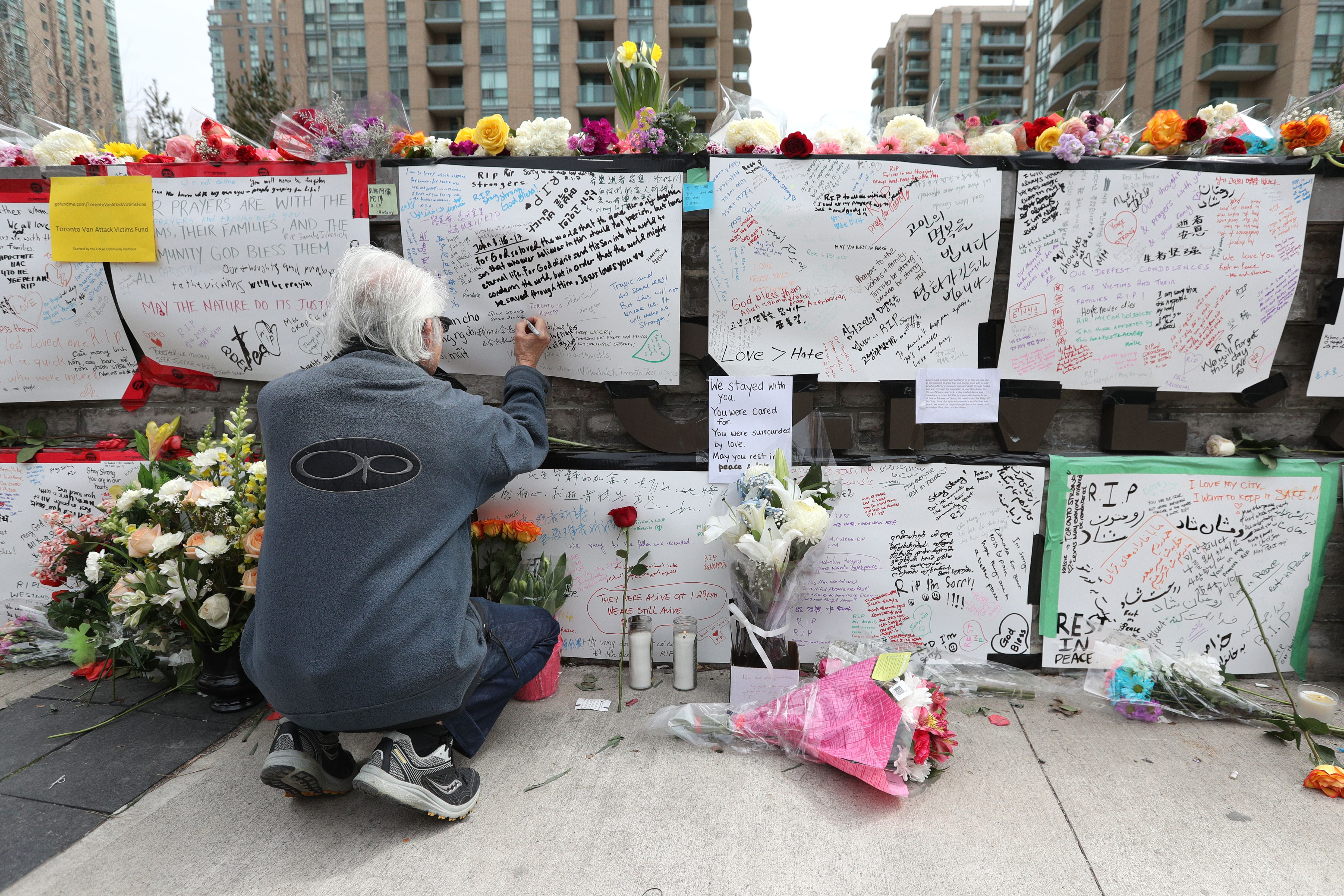 Jack Young leaves a notes on April 24, 2018, at a makeshift memorial for victims in the van attack in Toronto, Ontario.(LARS HAGBERG/AFP via Getty Images)