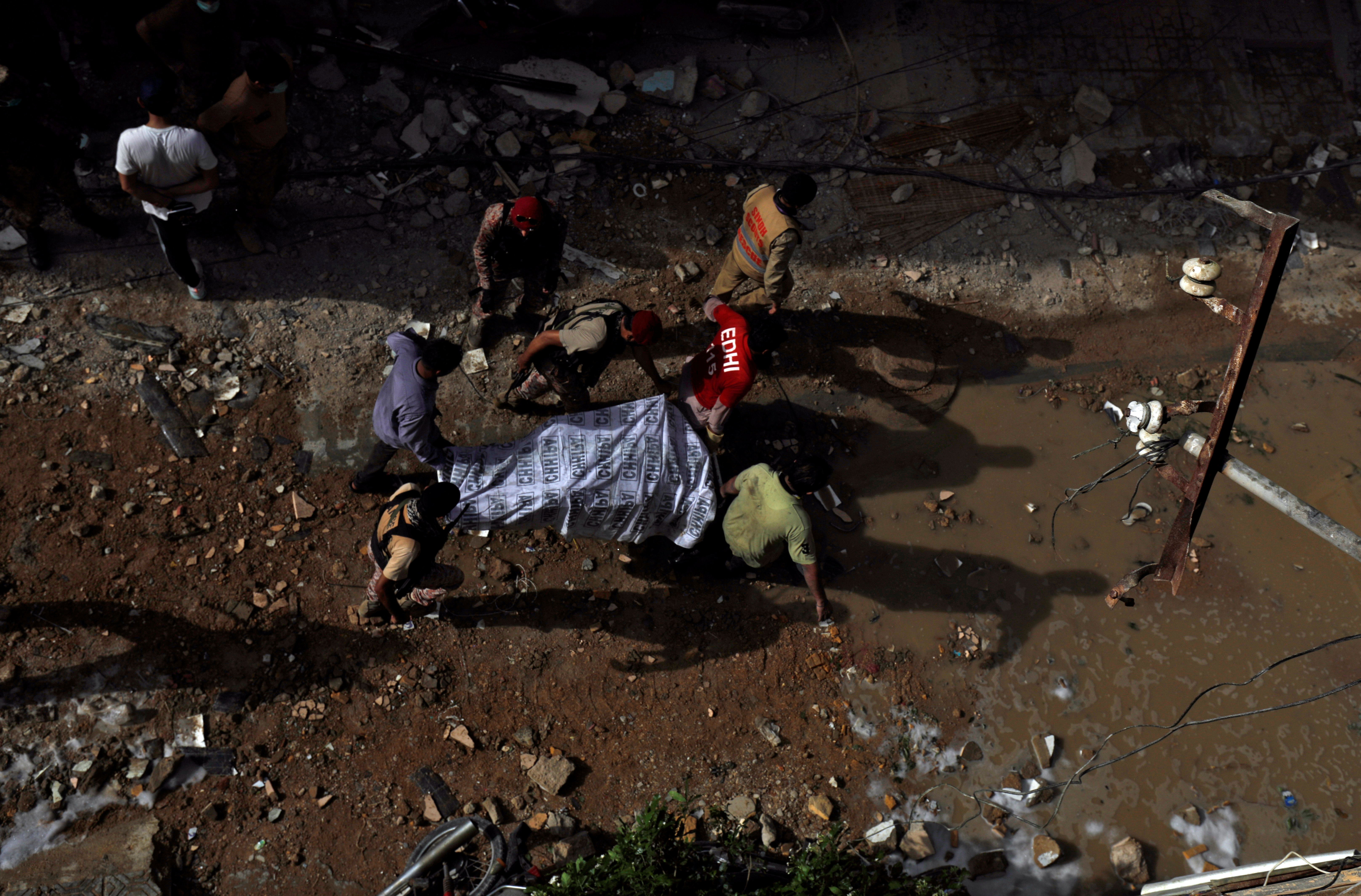 Rescue workers carry a victim at the site of a passenger plane crash in a residential area near an airport in Karachi, Pakistan May 22, 2020. REUTERS/Akhtar Soomro - RC2OTG90IHMN