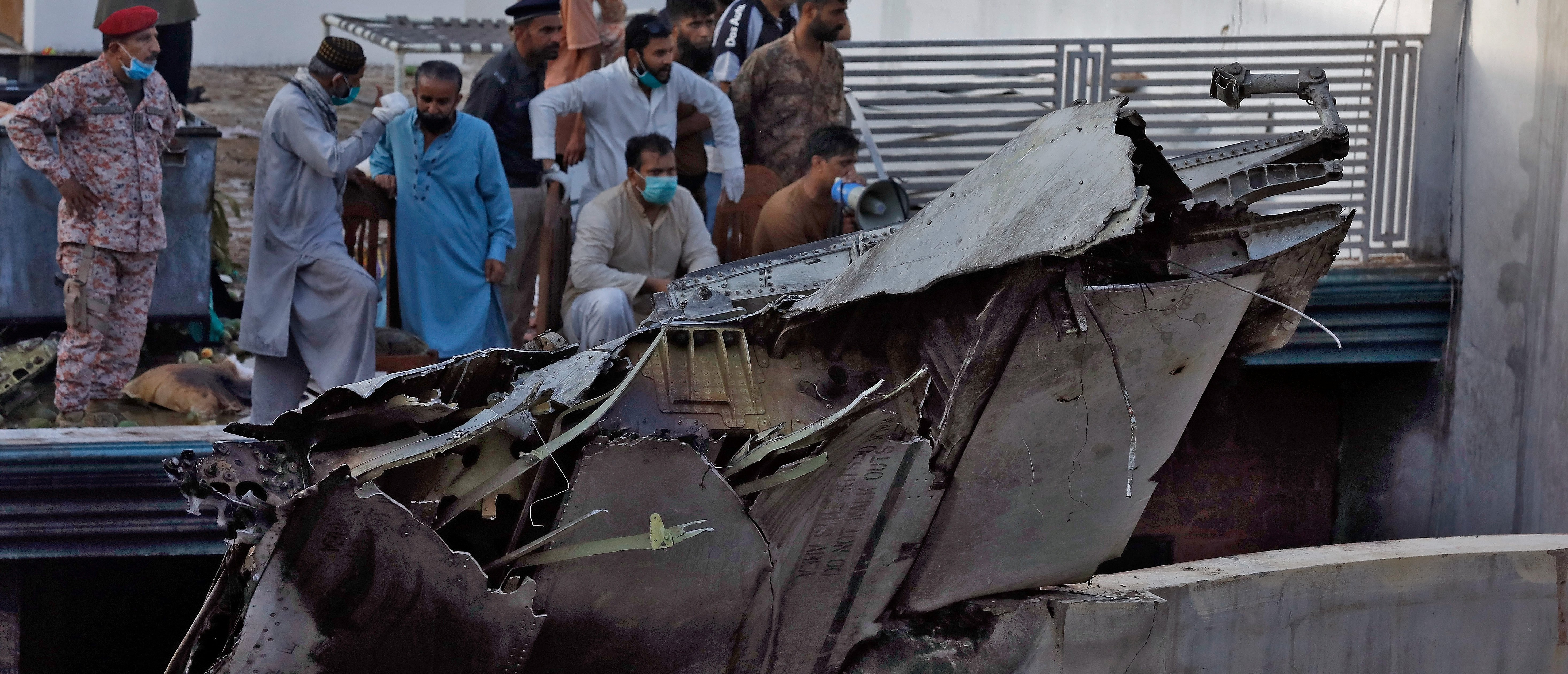 People stand next to the debris of a plane after crashed in a residential area near an airport in Karachi, Pakistan May 22, 2020. REUTERS/Akhtar Soomro - RC2PTG9N20SG