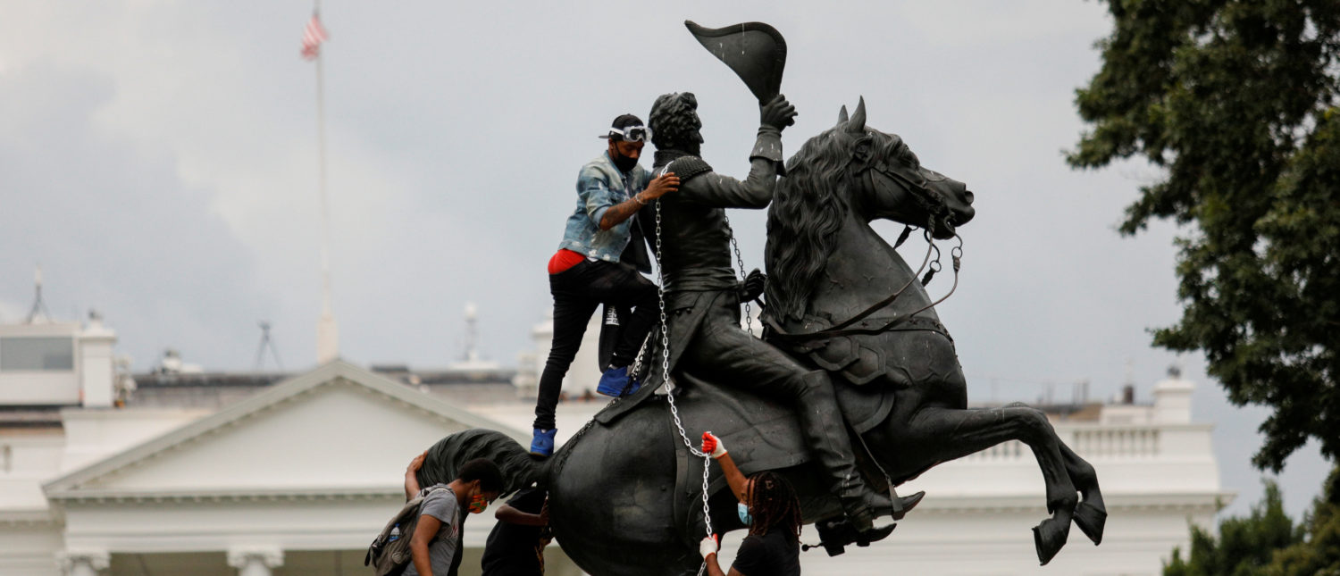 FILE PHOTO: Protestors attach a chain to the statue of U.S. President Andrew Jackson in the middle of Lafayette Park in front of the White House in an attempt to pull it down as someone throws a roll of toilet paper at the statue during racial inequality protests in Washington, D.C., U.S., June 22, 2020. REUTERS/Tom Brenner/File Photo