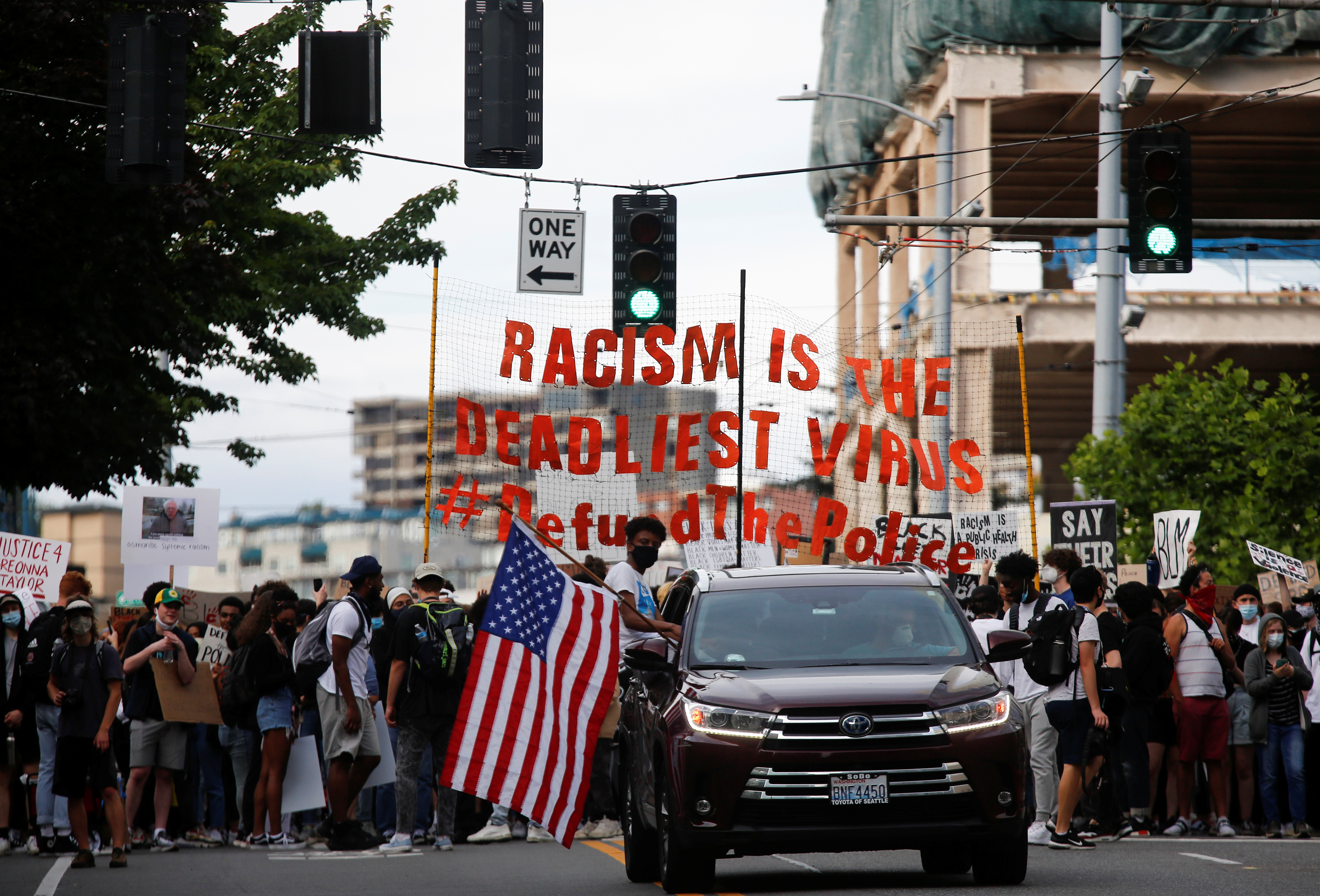 A protester sits out of the window of a car with an American flag as a youth-led protest group walks towards the Seattle Police Department's West Precinct in Seattle, Washington, U.S. June 10, 2020. REUTERS/Lindsey Wasson