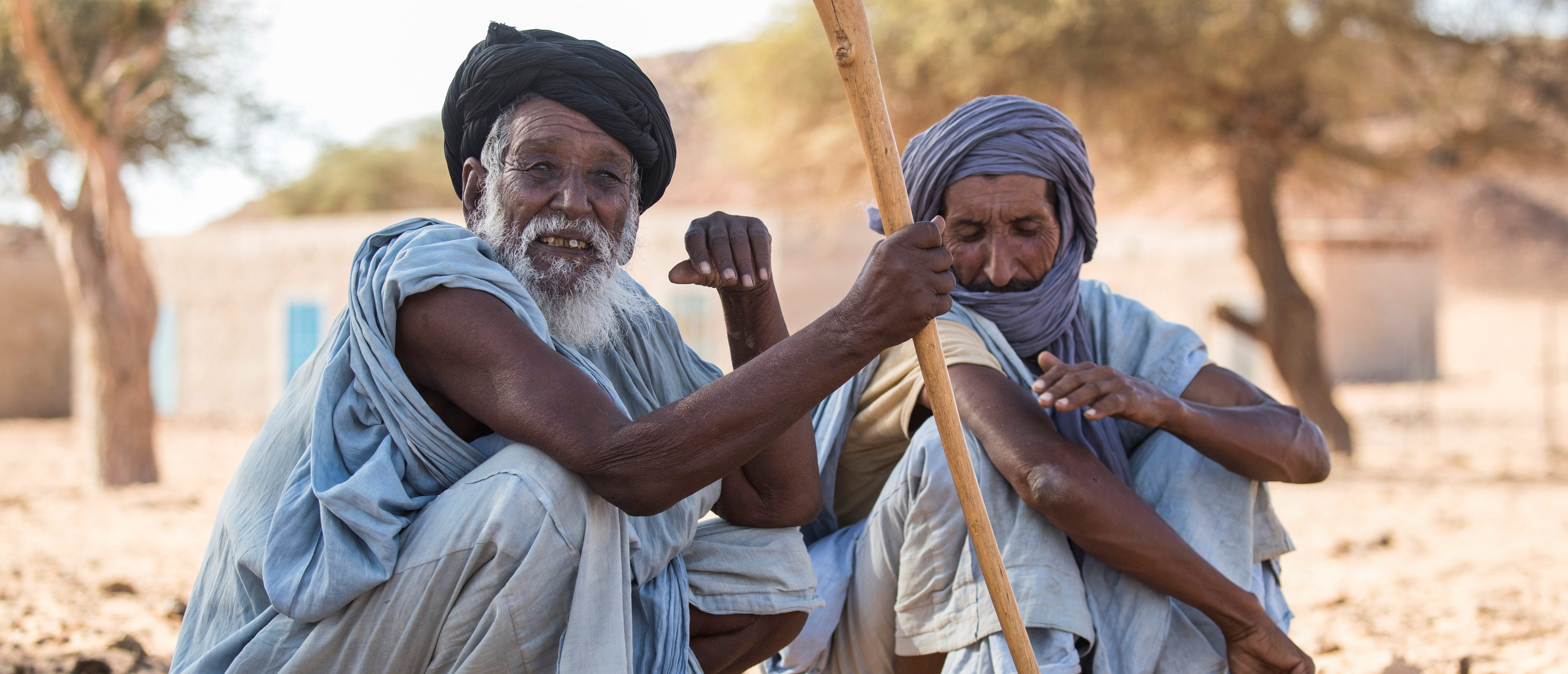 Men sit on the ground in Ouad Initi, eastern Mauritania, on November 21, 2018. - The Old Cities Festival takes place in Oualata from November 20 to November 26, 2018. (Photo by Thomas SAMSON / AFP) (Photo credit should read THOMAS SAMSON/AFP via Getty Images)