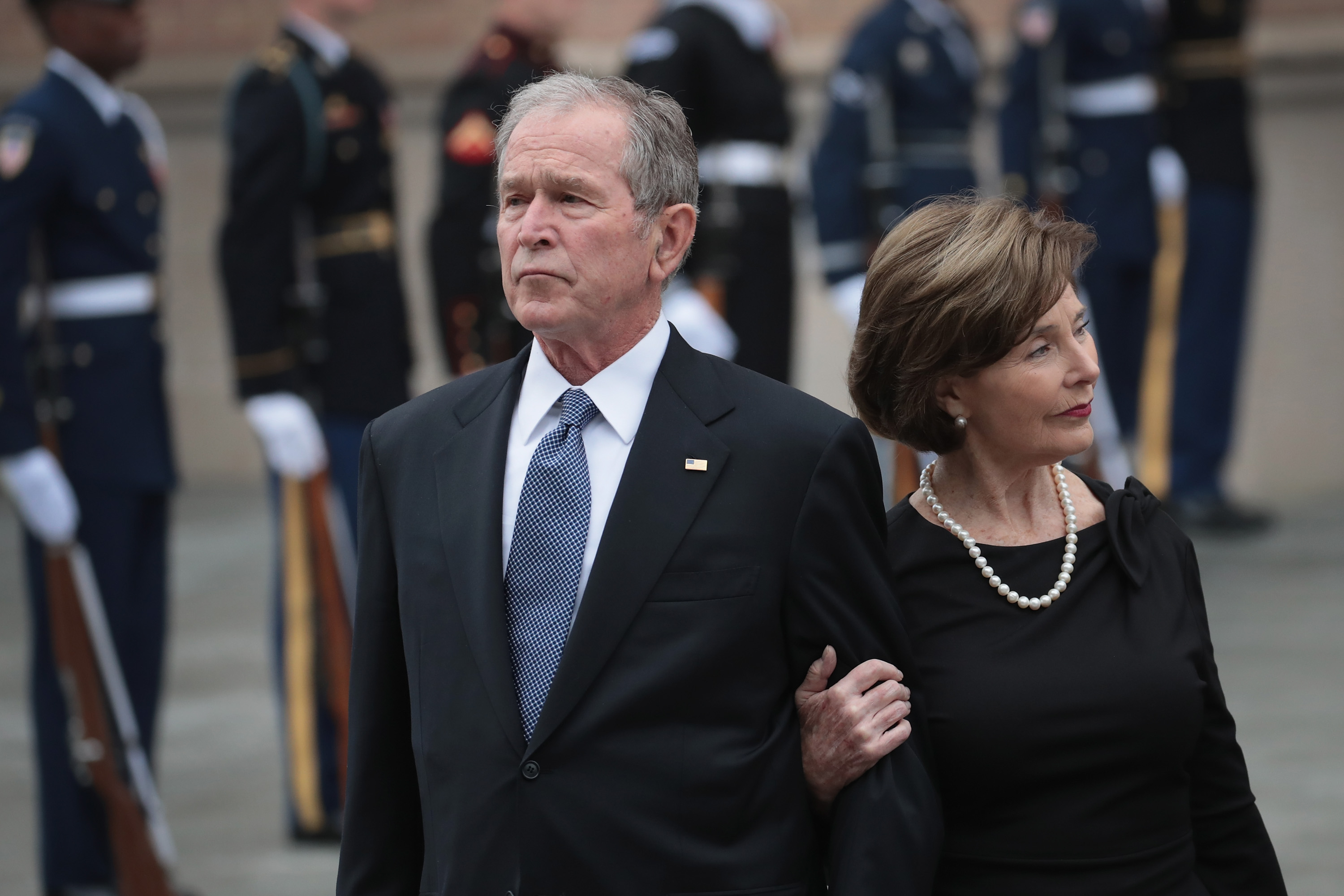 Former President George W. Bush and his wife Laura watch as the honor guard passes after loading the casket of President George H.W. Bush into a hearse outside St. Martin's Episcopal Church following his funeral service December 6, 2018 in Houston, Texas. (Scott Olson/Getty Images)