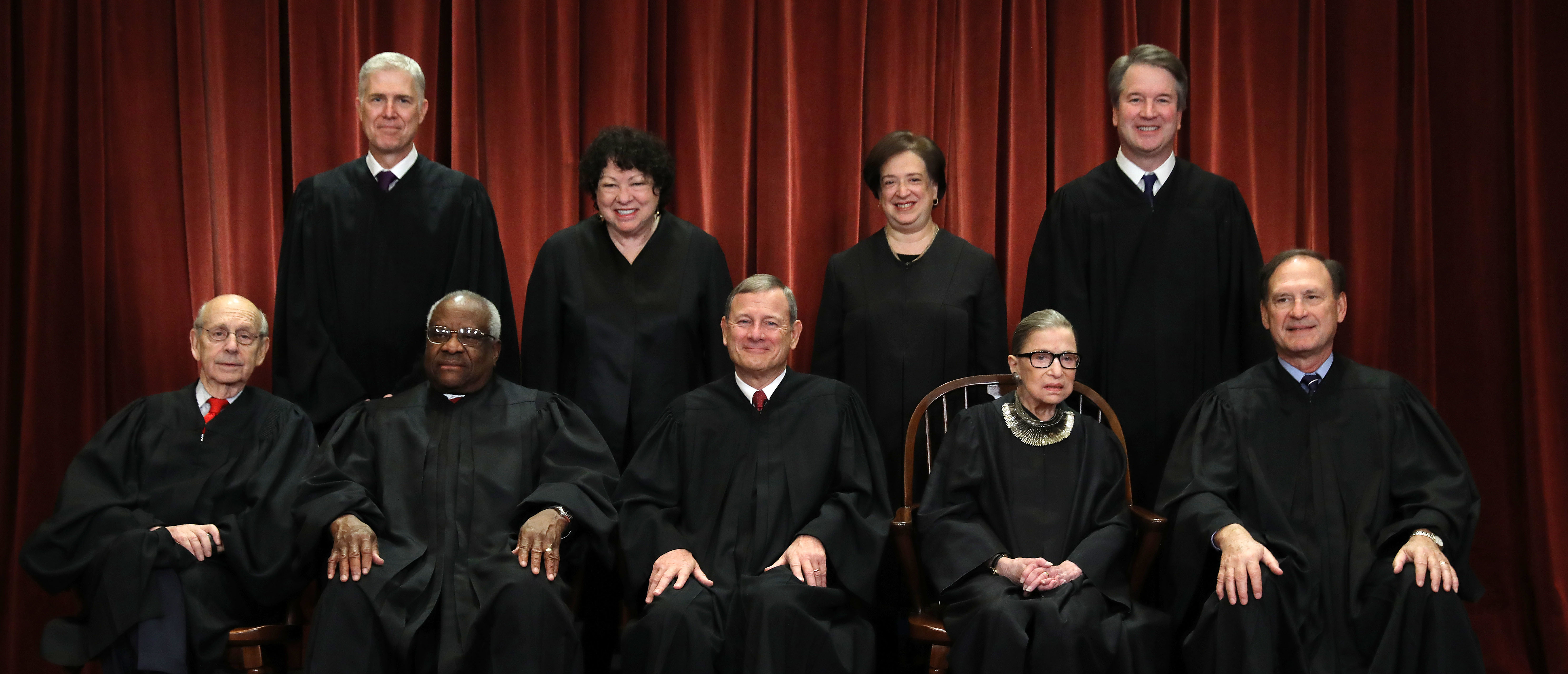 """WASHINGTON, DC - NOV. 30: United States Supreme Court (Front L-R) Associate Justice Stephen Breyer, Associate Justice Clarence Thomas, Chief Justice John Roberts, Associate Justice Ruth Bader Ginsburg, Associate Justice Samuel Alito, Jr., (Back L-R) Associate Justice Neil Gorsuch, Associate Justice Sonia Sotomayor, Associate Justice Elena Kagan and Associate Justice Brett Kavanaugh pose for their official portrait at the in the East Conference Room at the Supreme Court building Nov. 30, 2018 in Washington, DC. Earlier this month, Chief Justice Roberts publicly defended the independence and integrity of the federal judiciary against President Trump after he called a judge who had ruled against his administration's asylum policy """"an Obama judge."""" """"We do not have Obama judges or Trump judges, Bush judges or Clinton judges,"""" Roberts said in a statement. """"What we have is an extraordinary group of dedicated judges doing their level best to do equal right to those appearing before them. That independent judiciary is something we should all be thankful for."""" (Photo by Chip Somodevilla/Getty Images)"""